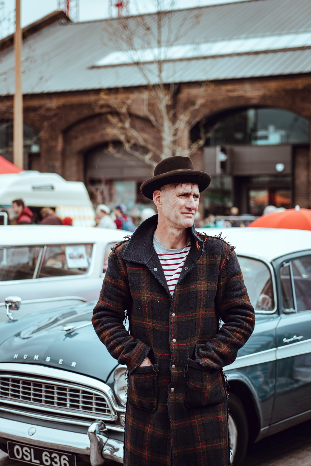 man wearing plaid button-up coat in front of classic car