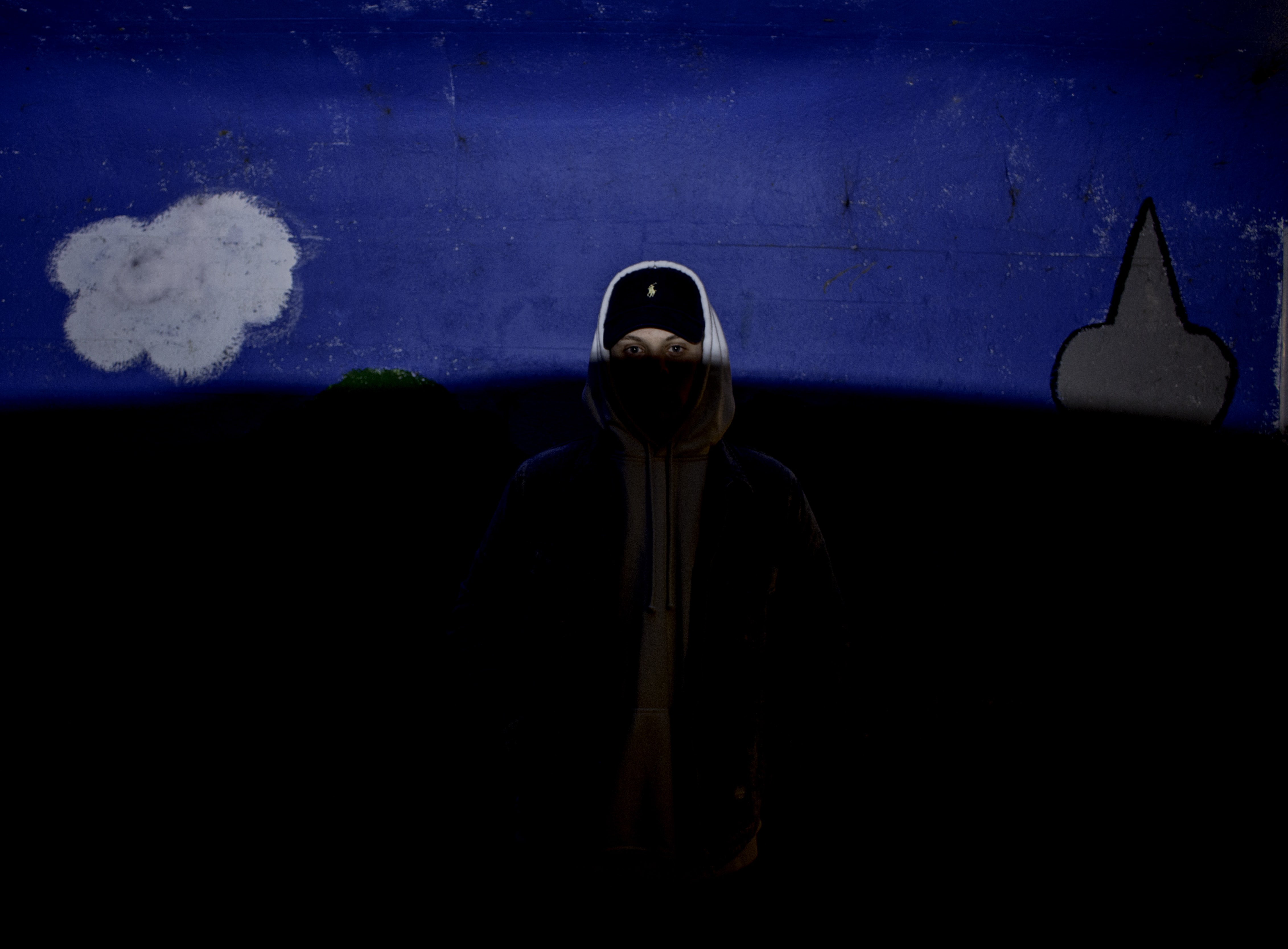 Person in a hoodie and hat standing in the shadows with only their face lit