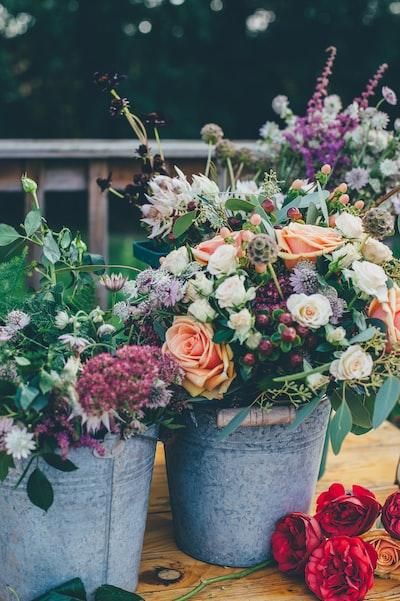 assorted flowers on gray metal bucket