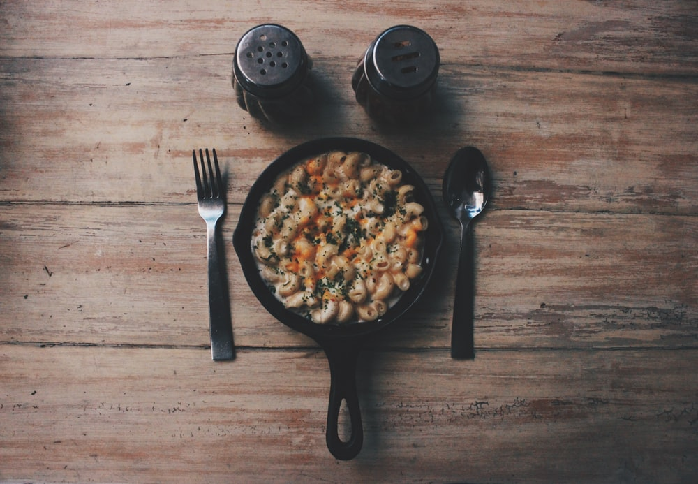 cooked food on black plate beside fork and spoon on brown wooden table