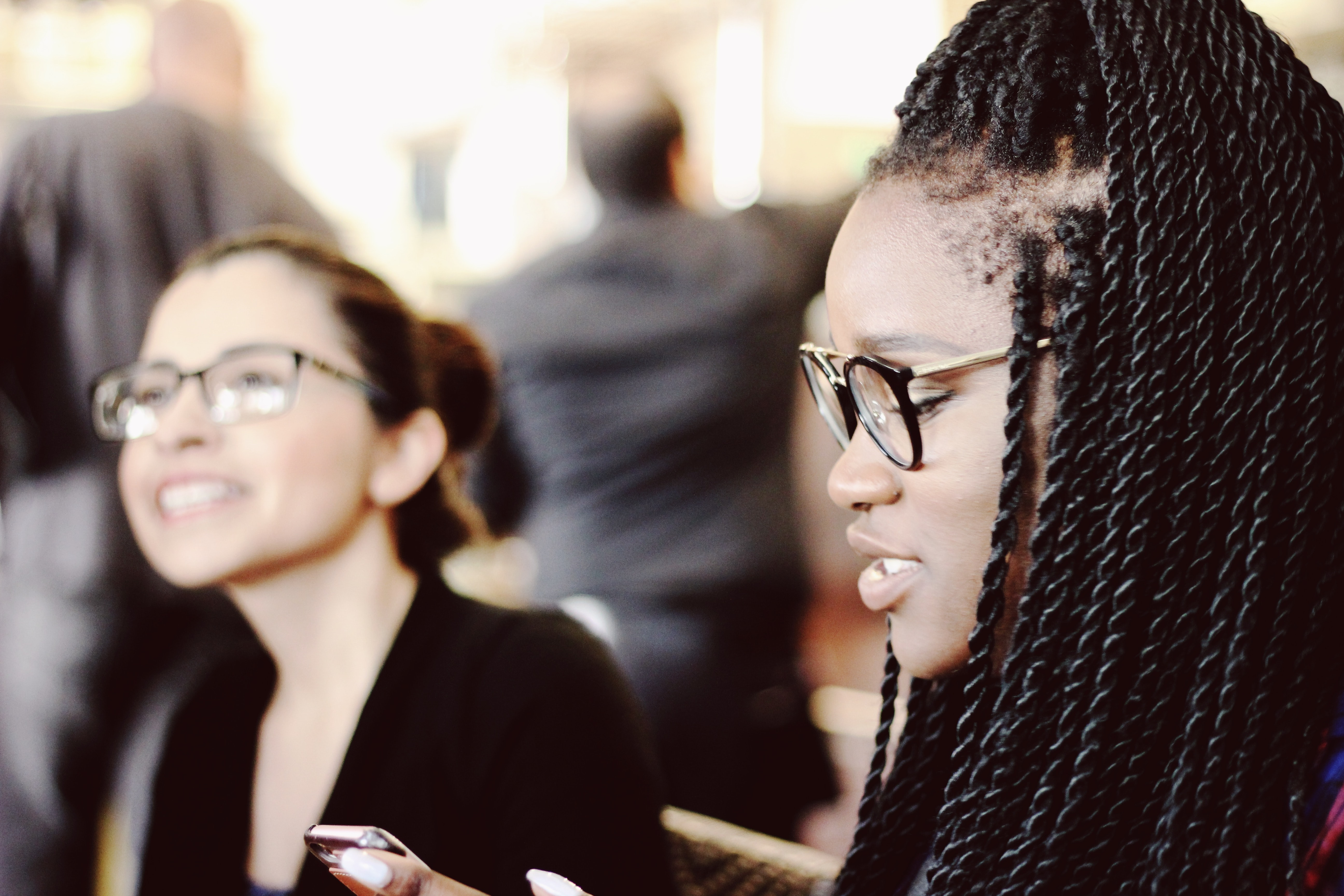 An African American girl with braids and glasses next to an Asian girl with braids.