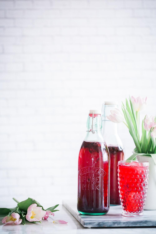 clear glass bottle beside purple flowers