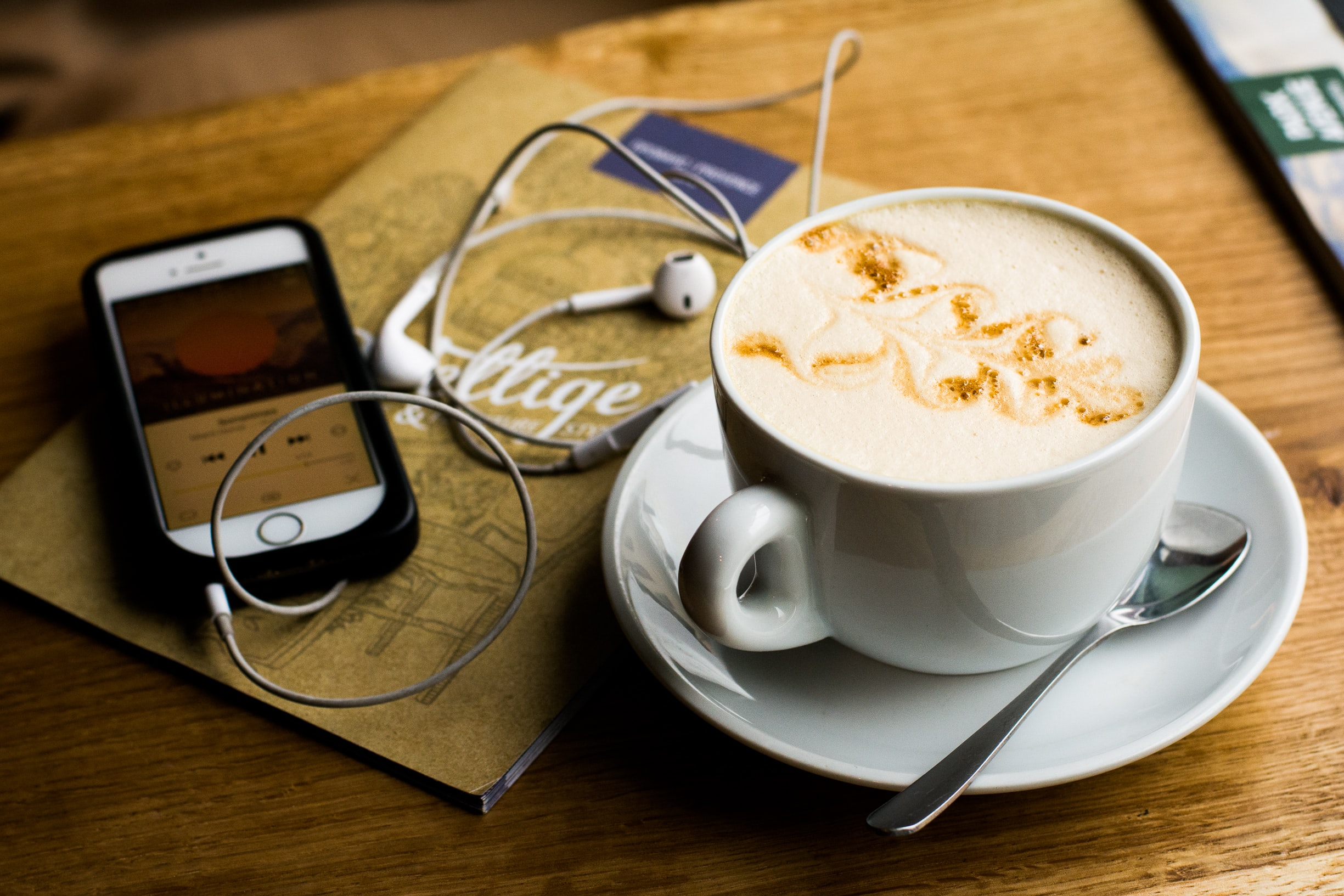A cup of latte and an iPhone with a music app open on a table