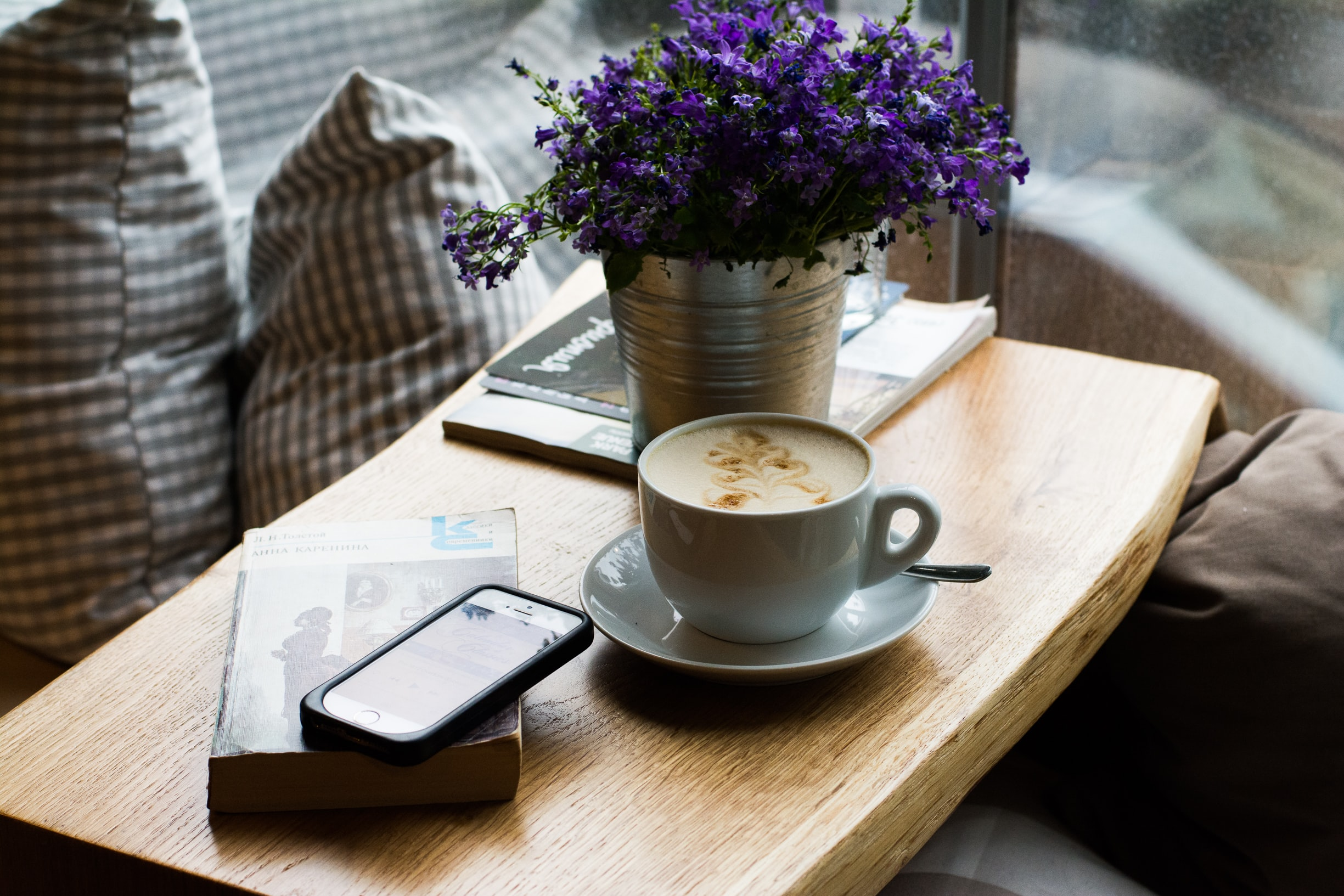 A cup of coffee with latte art on a coffee table next to an iPhone, a purple bouquet and a book