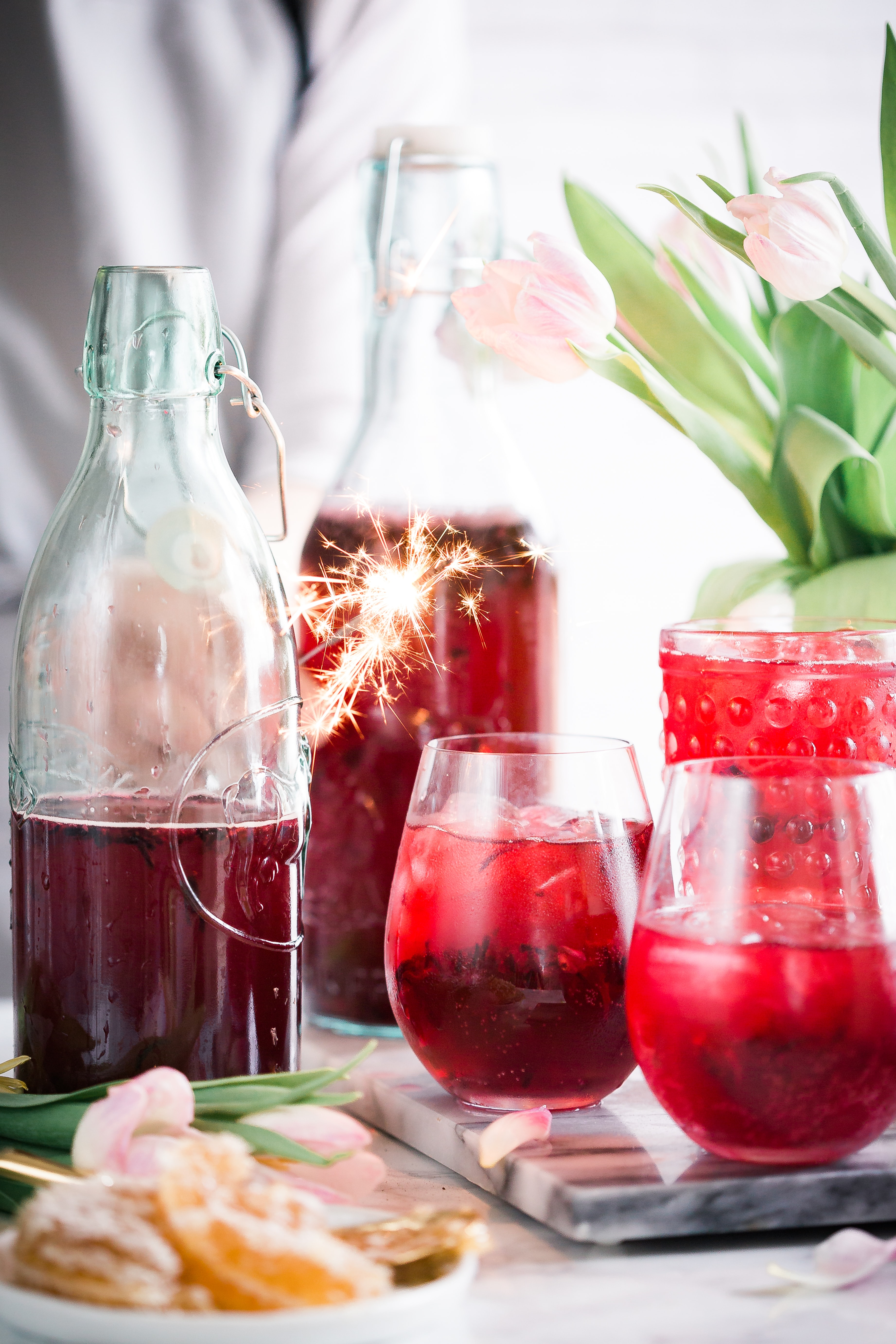 Bottles and glasses with a red beverage next to flowers and a platter of citruses on a tabletop