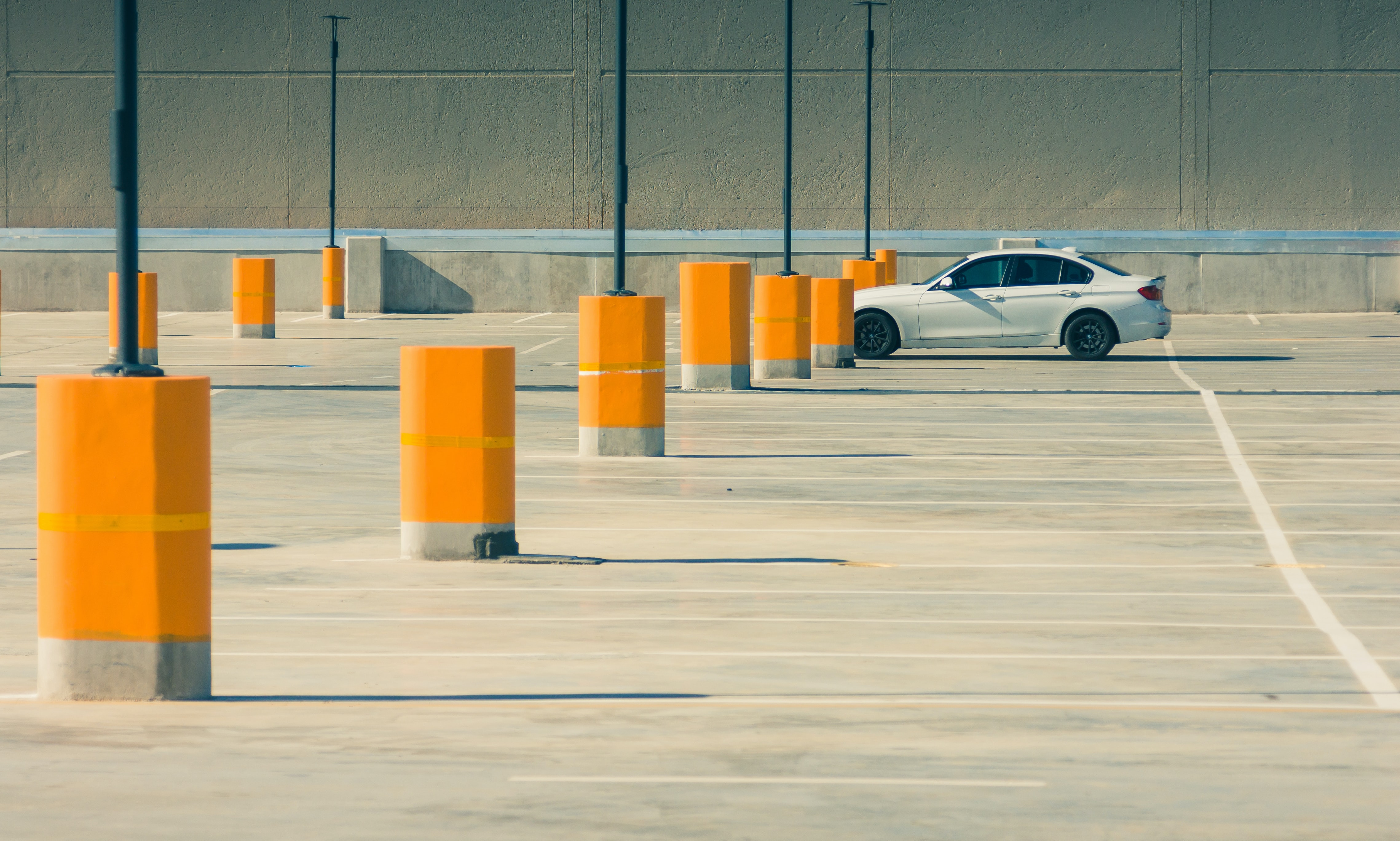Wide angle shot of a lone white car in a large parking lot.