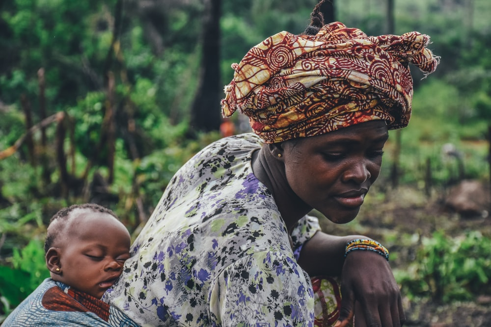 woman carrying baby on back