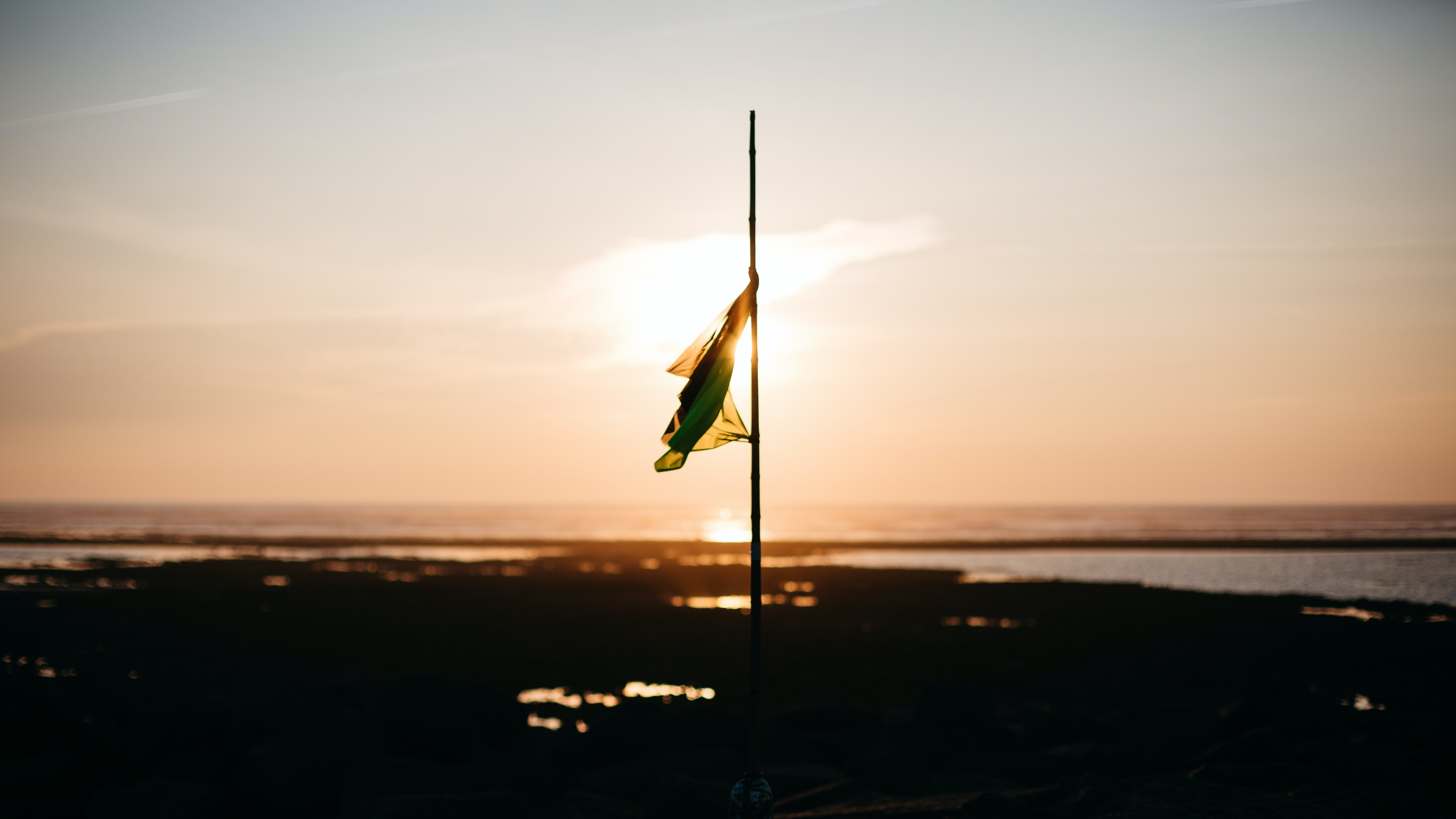 A flag at half mast on a flat shoreline with the sun setting behind it in Ars-en-Ré.