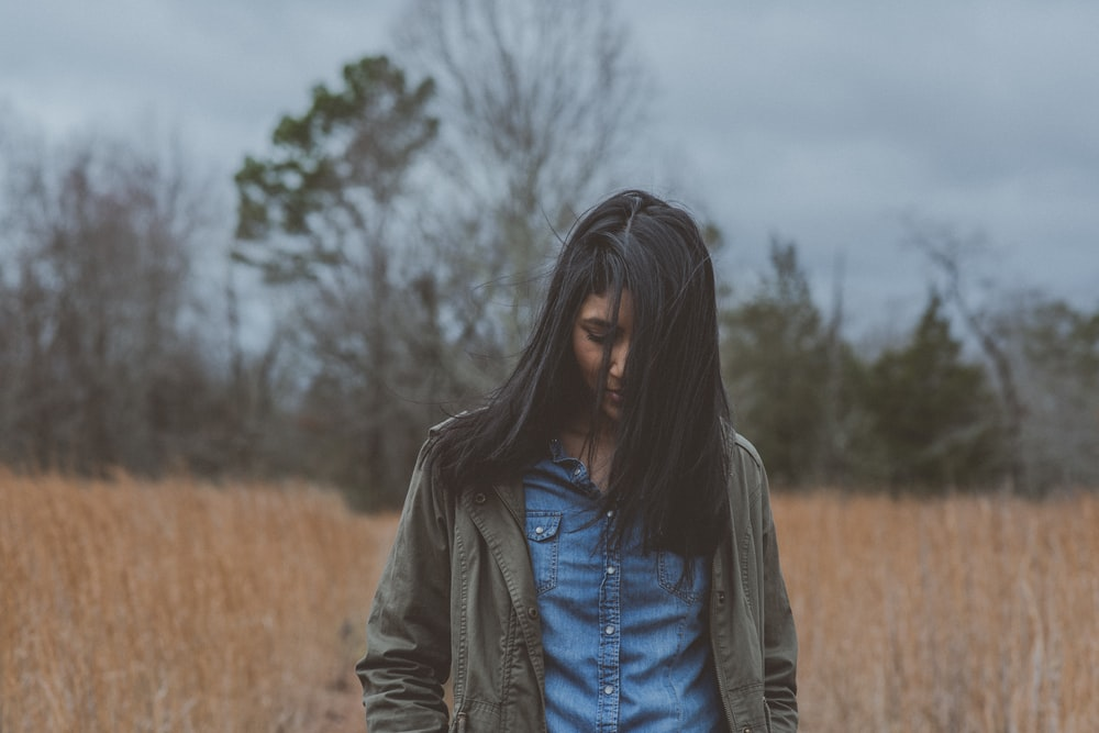 woman wearing gray cardigan surrounded grass