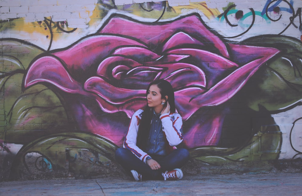 woman sitting beside purple flower wall painting