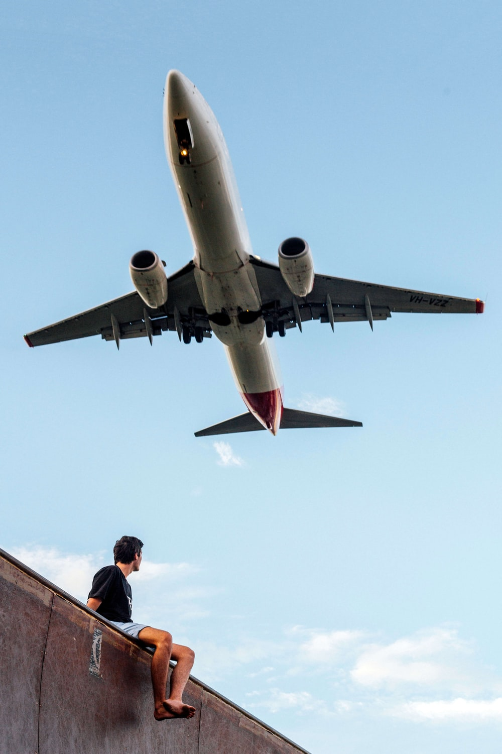 low angle photography of man wearing black shirt under white and gray airplane