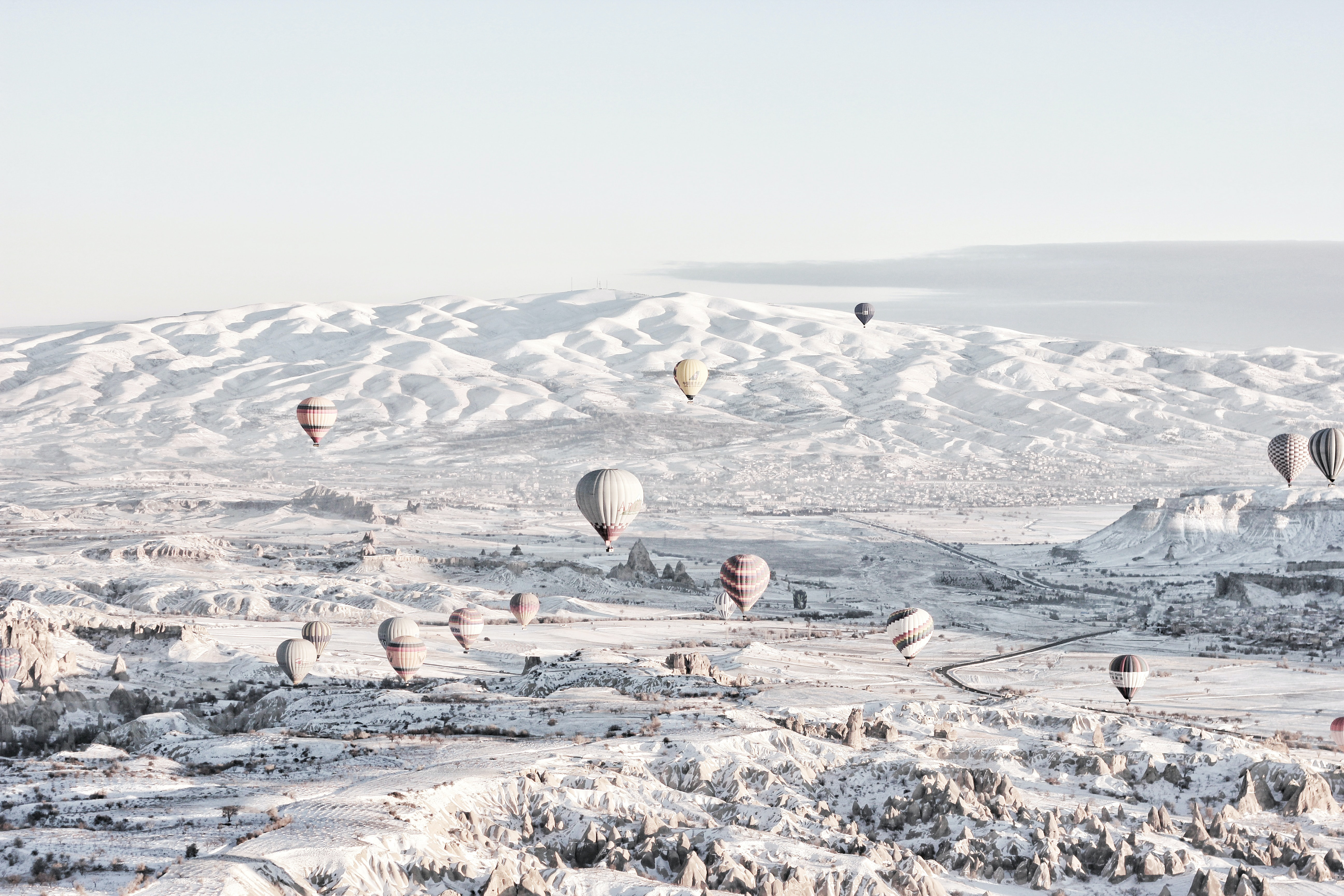 assorted-color air balloons below snowland at daytime