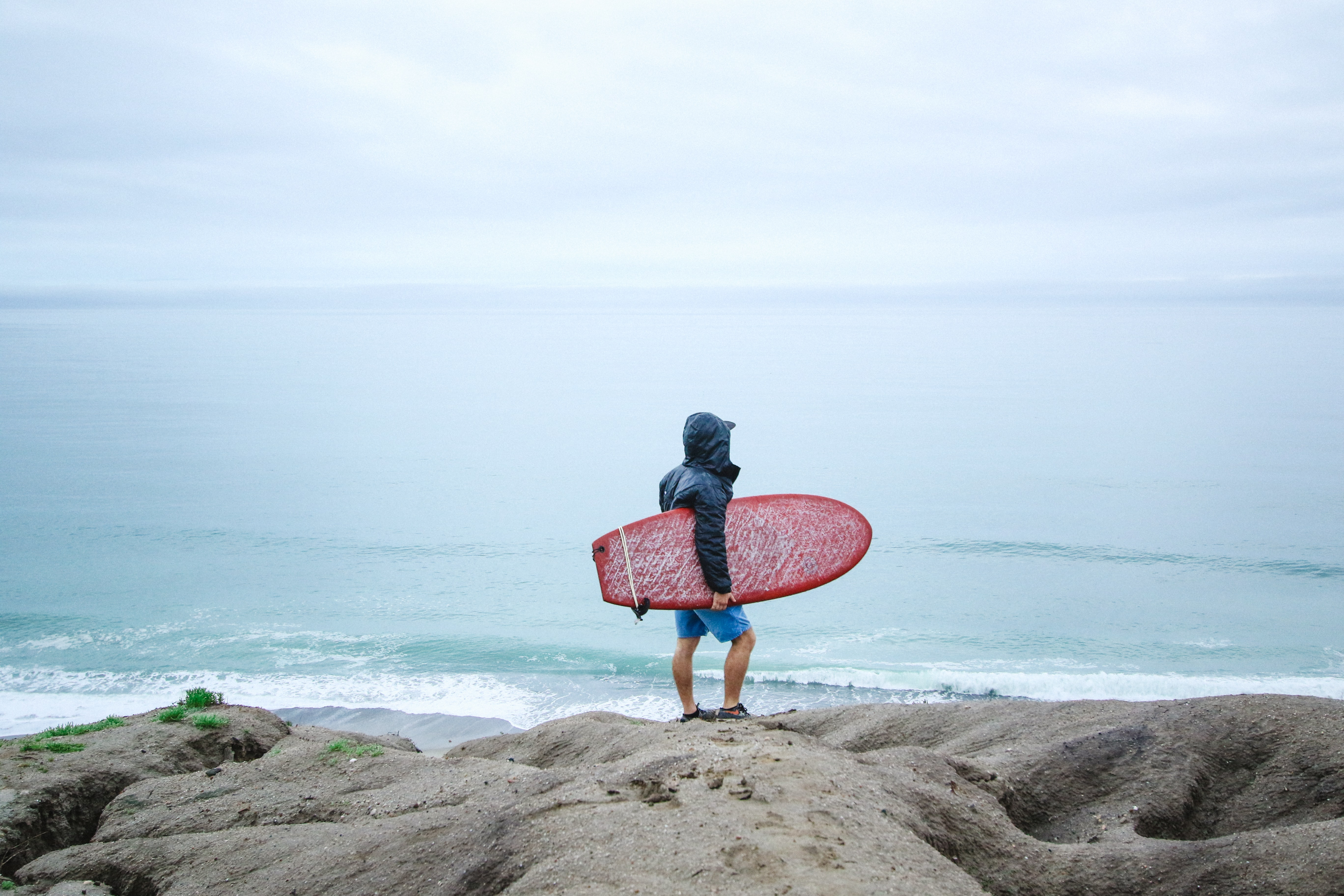 A man with his hood up standing on the a rocky coastline at San Clemente, carrying a red surfboard and looking out over the sea