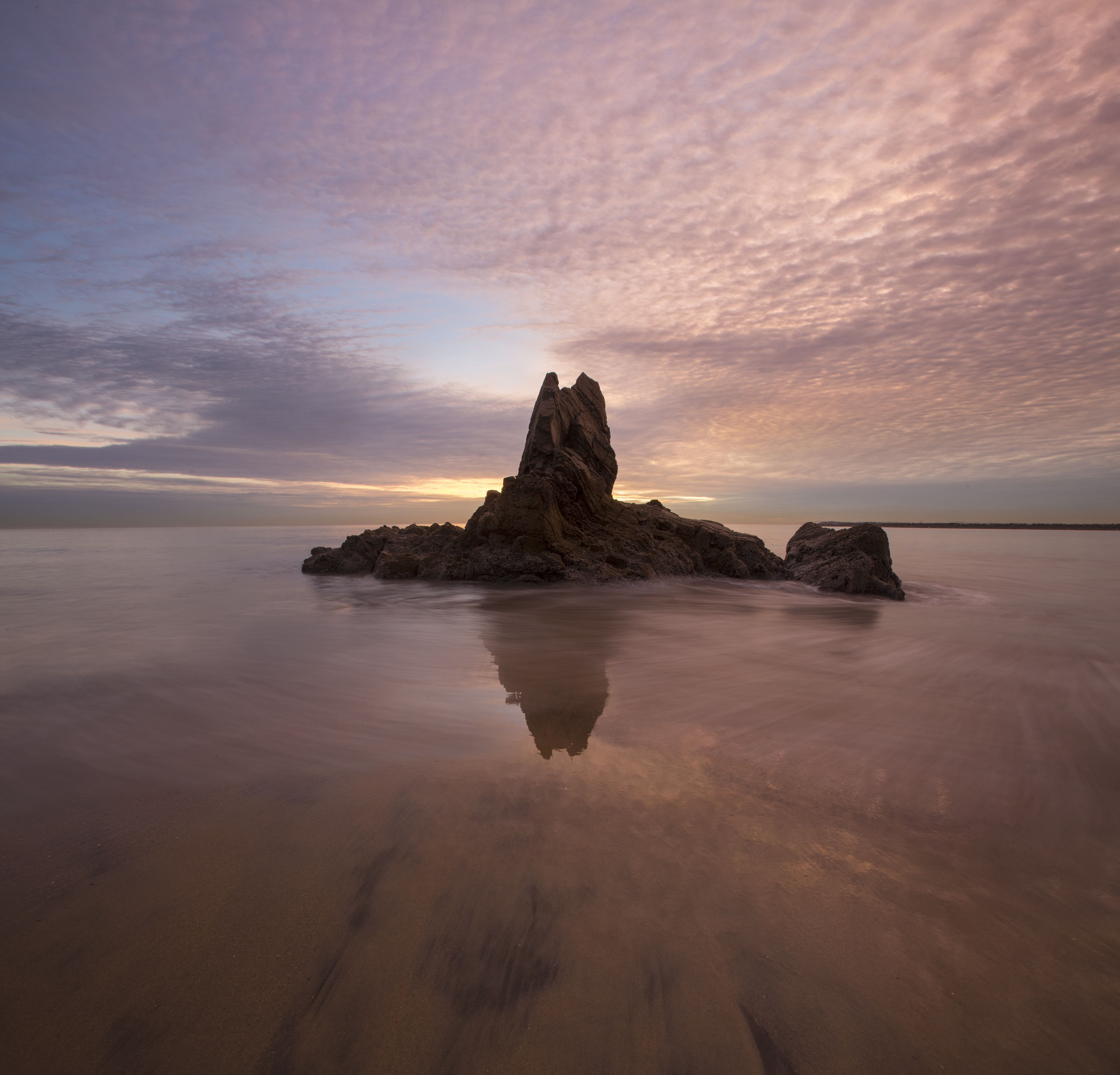 Island in Newport Beach, California standing between a sunset sky with patchy clouds and reflective waters