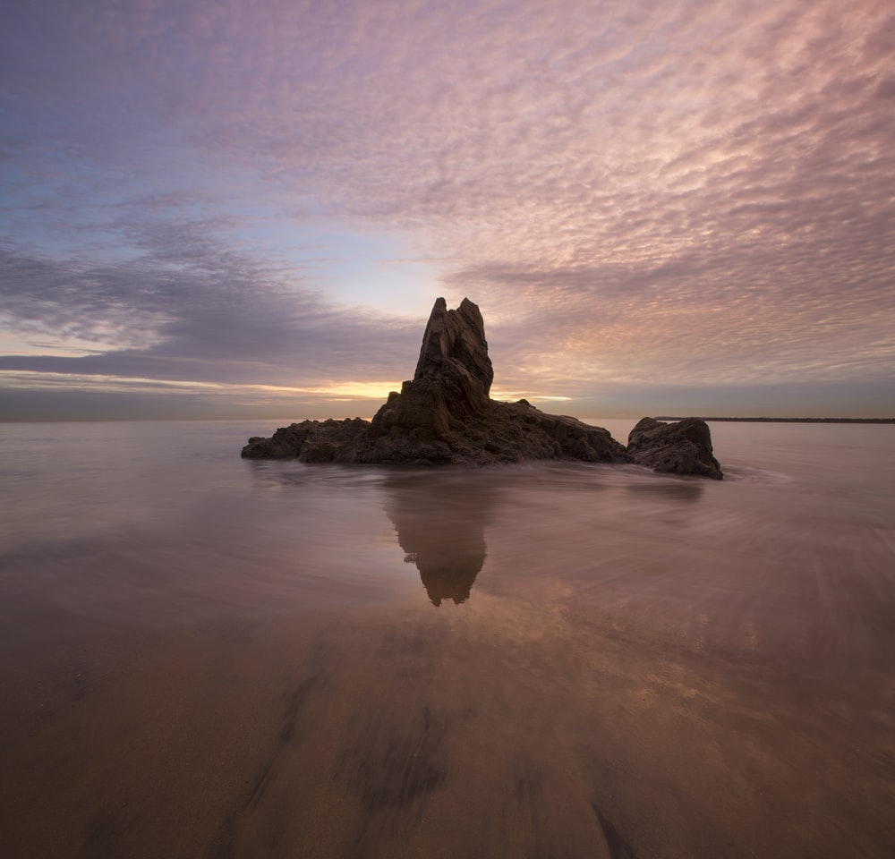 rock formation surrounded by water