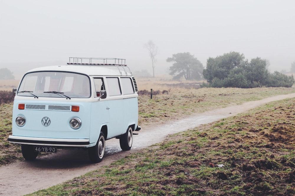 gray Volkswagen van parking in between green grass field