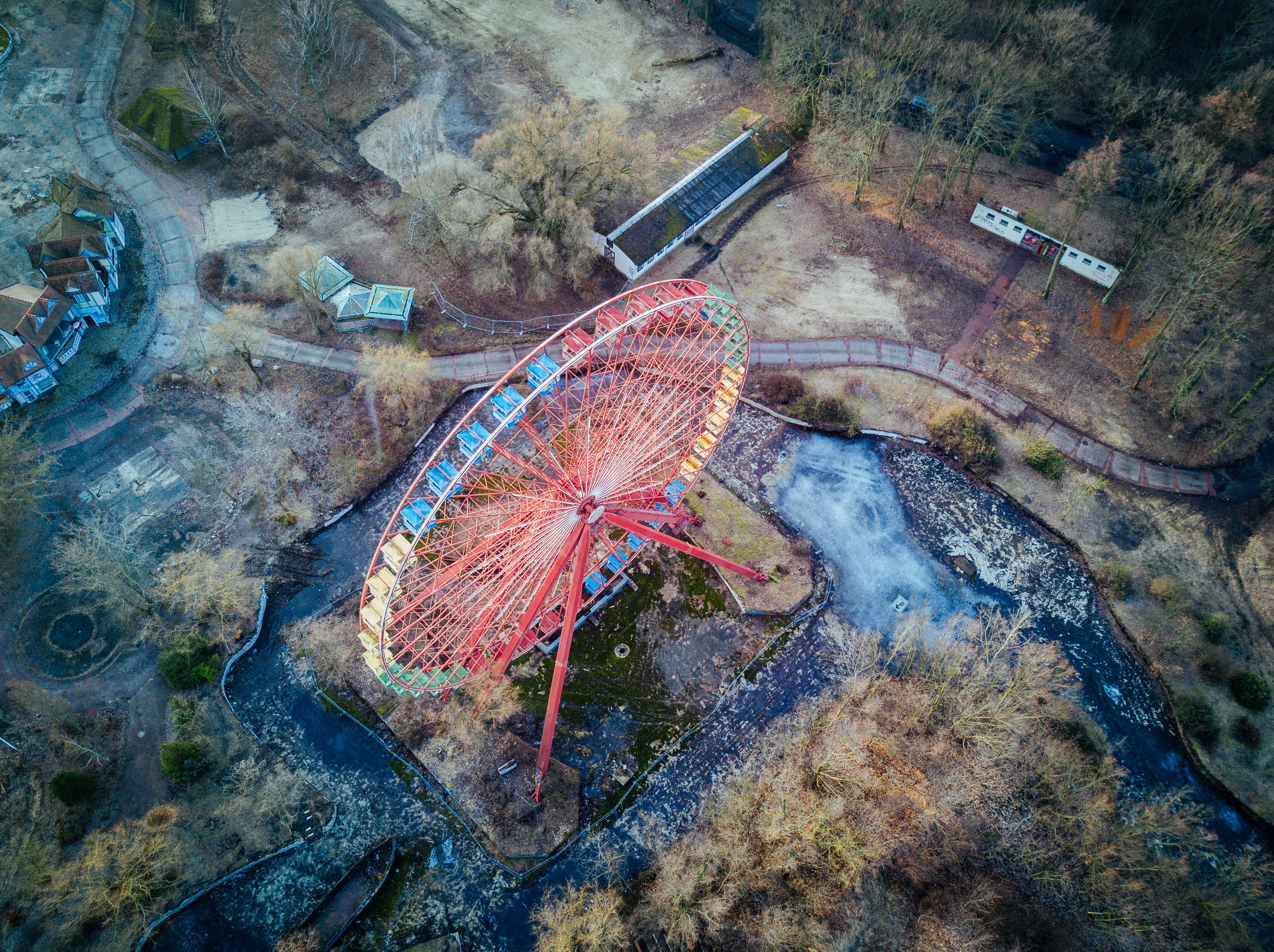 A drone shot of a red Ferris wheel in a desolate area