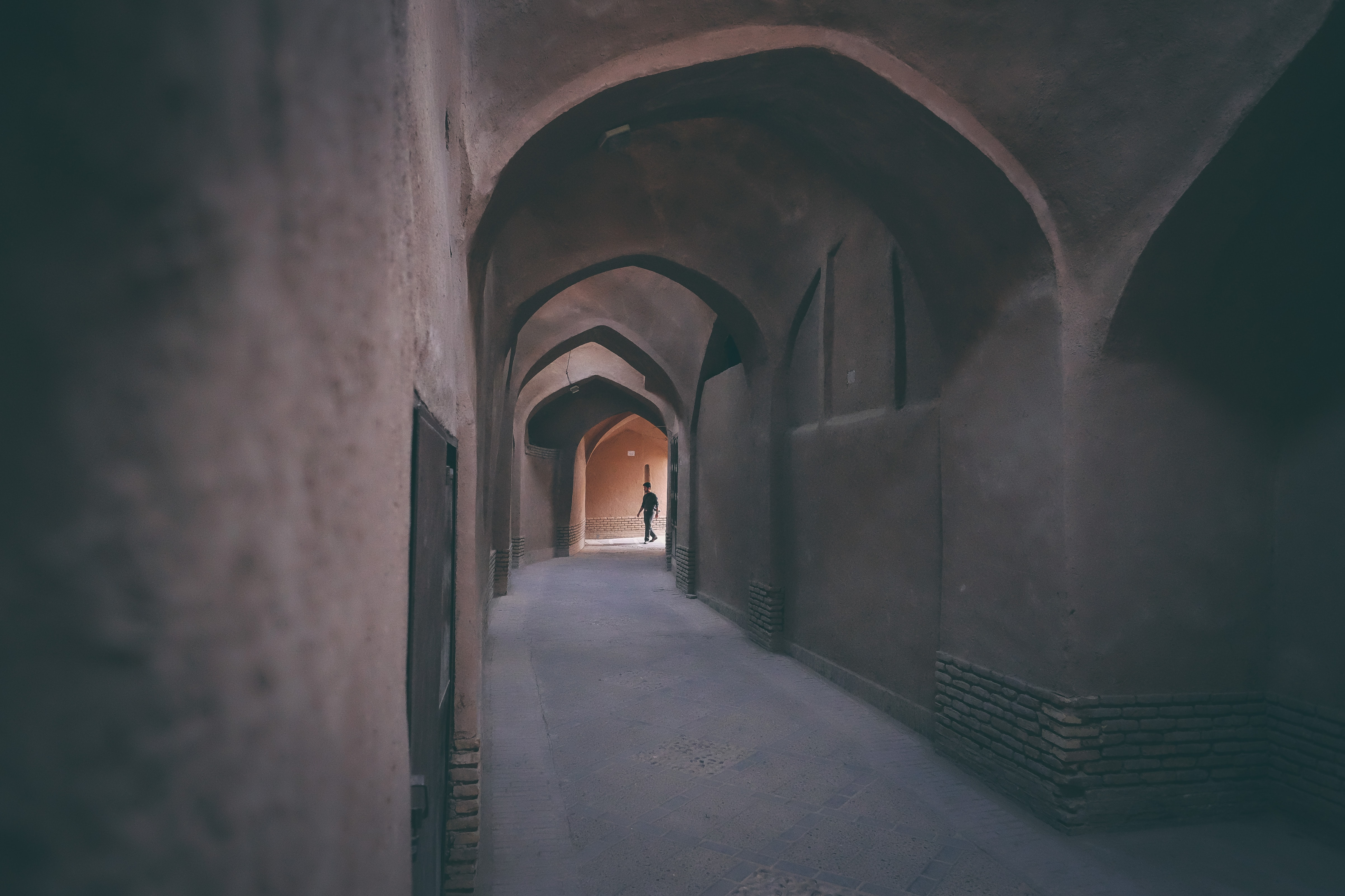A person walks through an empty arched passageway in an old town.