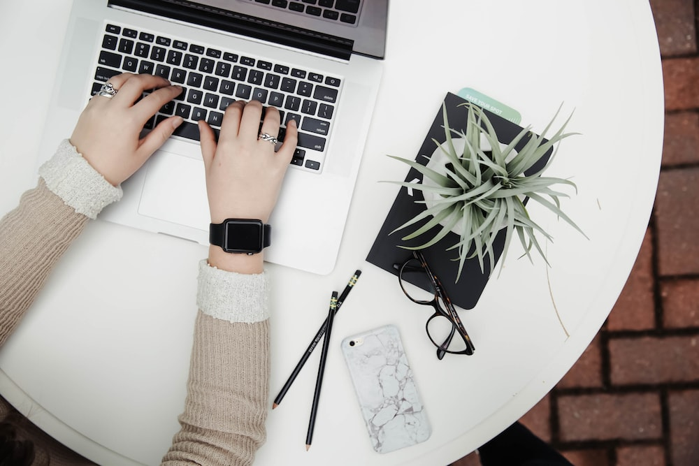 A person typing on a netbook with plants, pencils, a smartphone and glasses on the desk table