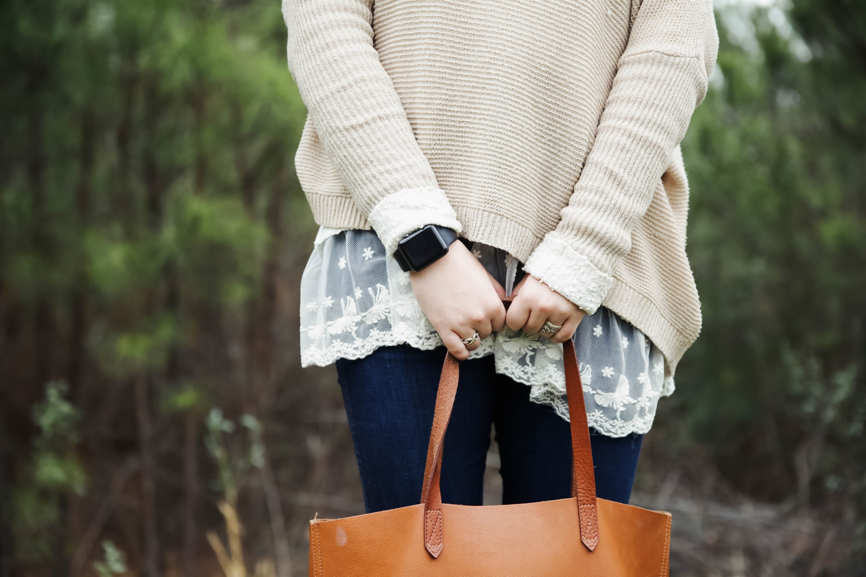 woman standing holding a brown leather tote bag