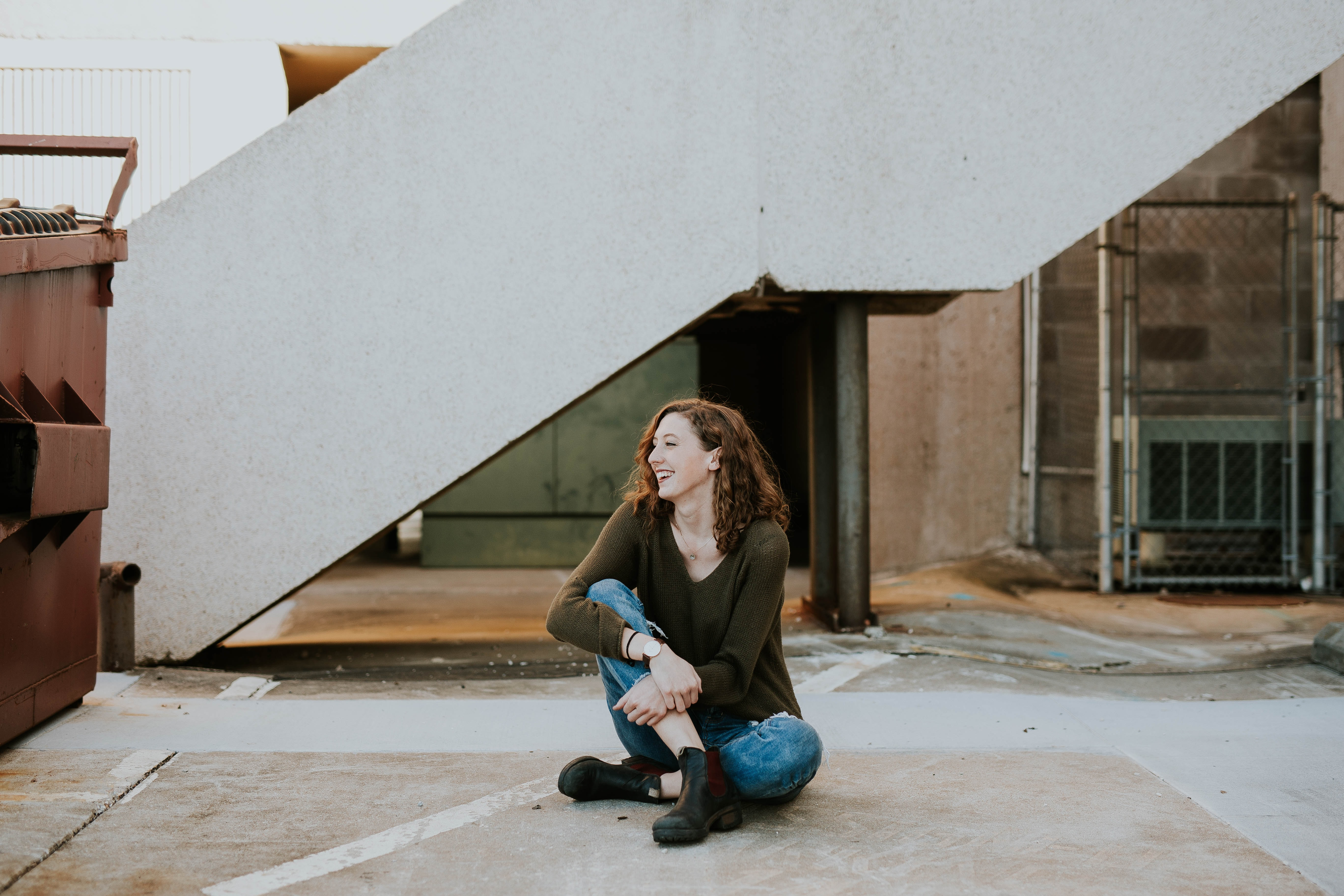 A woman laughing while sitting on a concrete floor