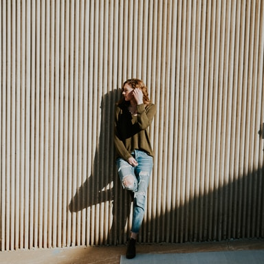 woman leaning on beige wall with shadow at daytime