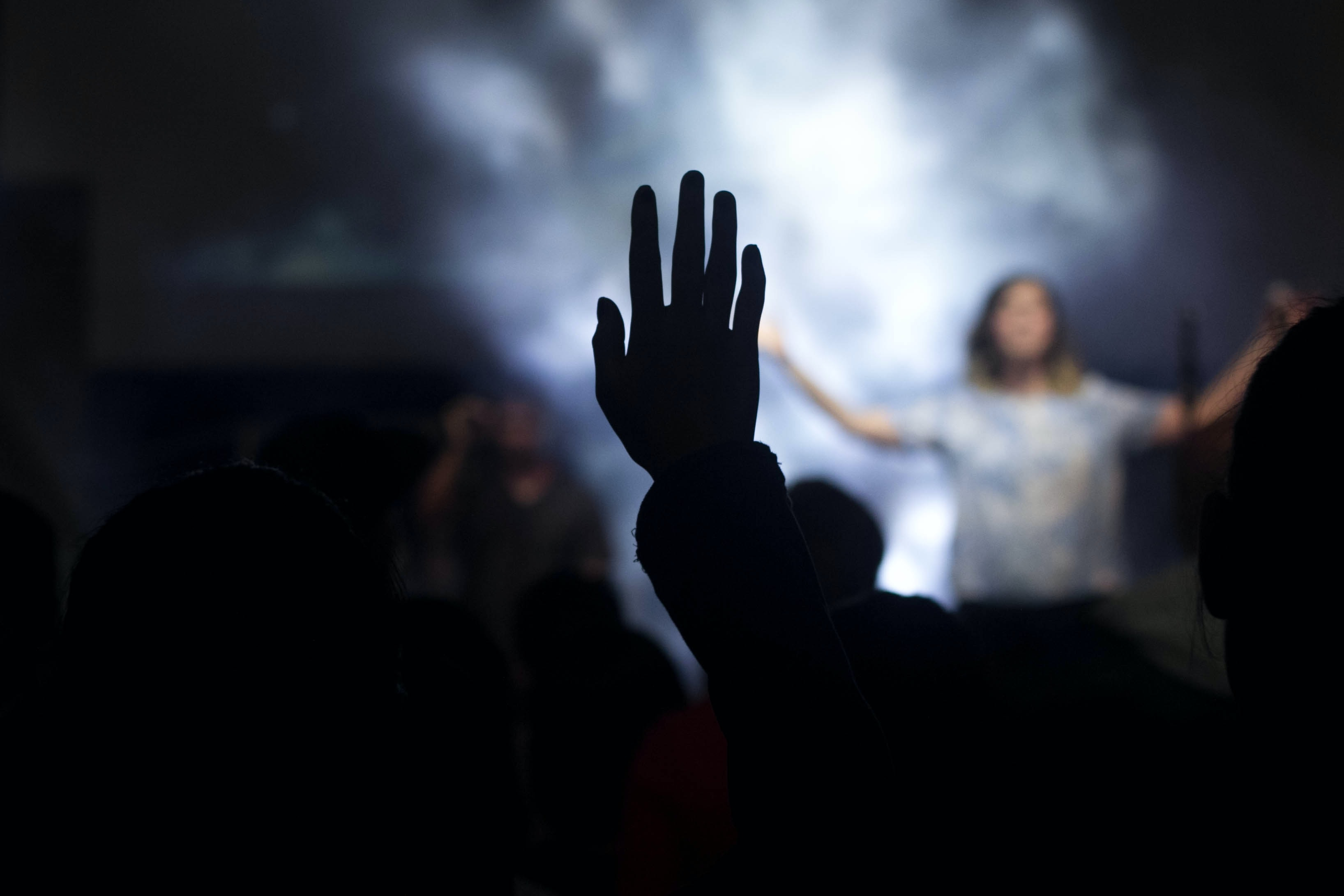 silhouette of person with right hand on air in front of woman on stage