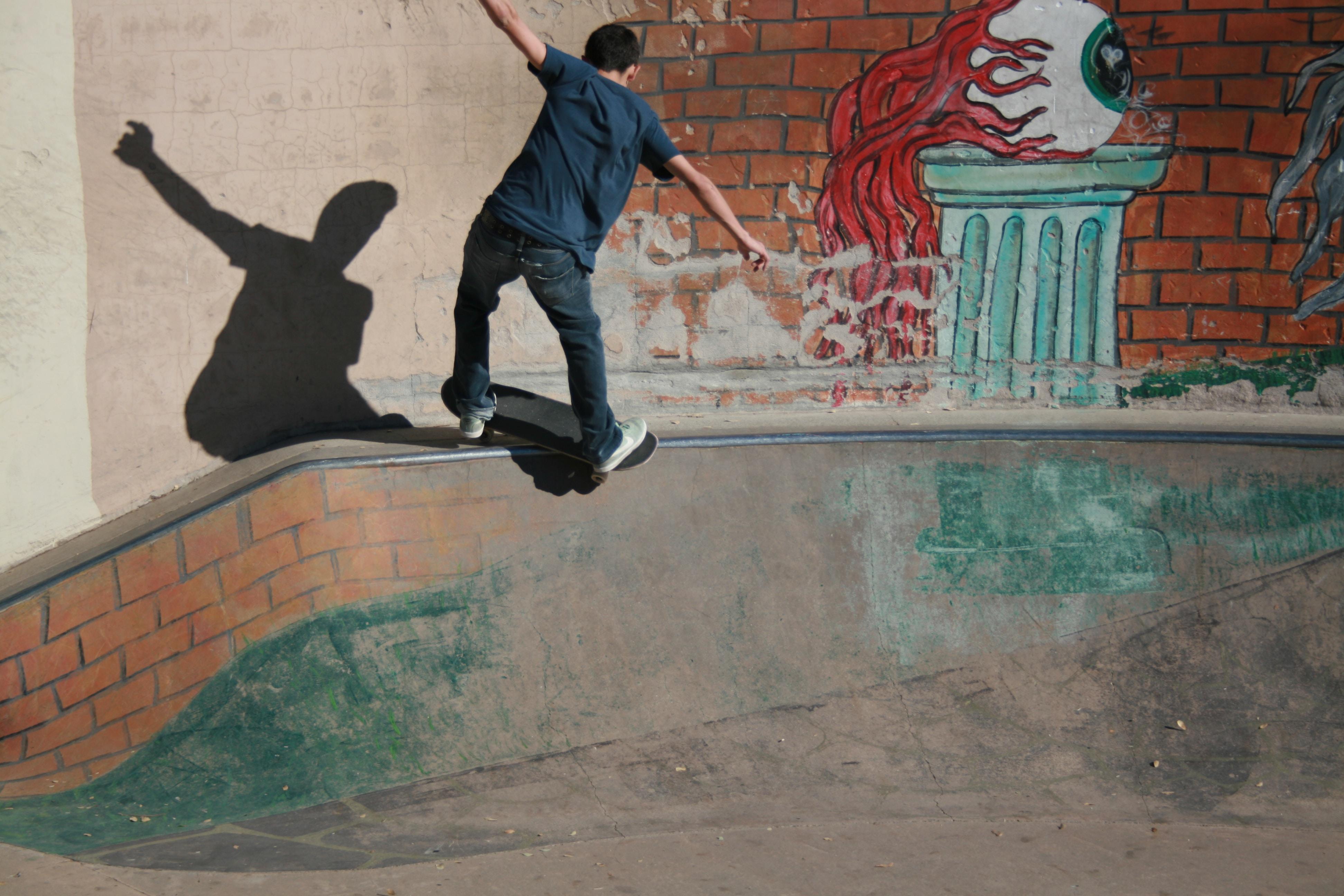 Skateboarder grinding on small ramp near eyeball graffiti at American River Canyon Overlook Park