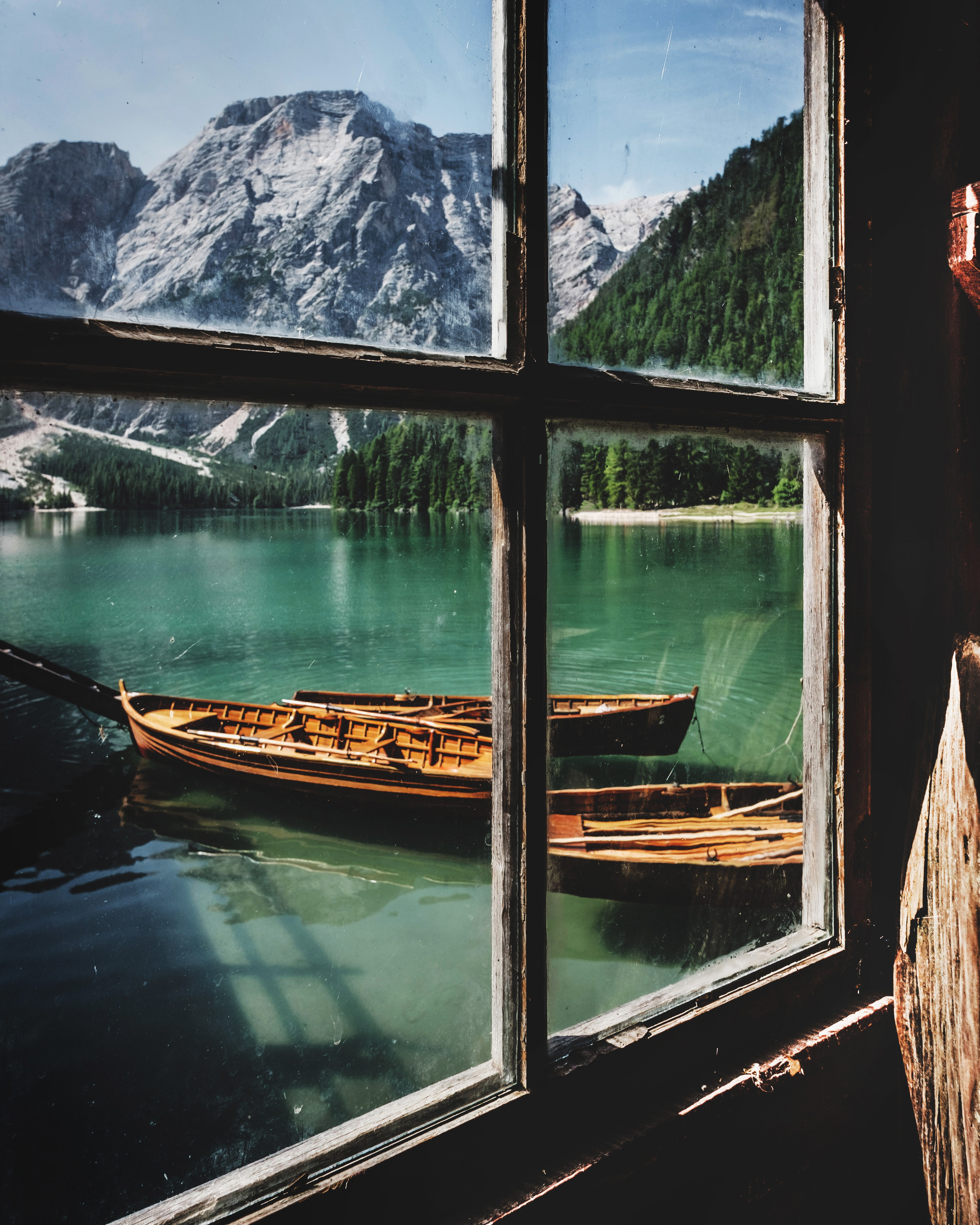 A window view looking at a pair of boats floating in the river with a mix of green and snow covered mountains.