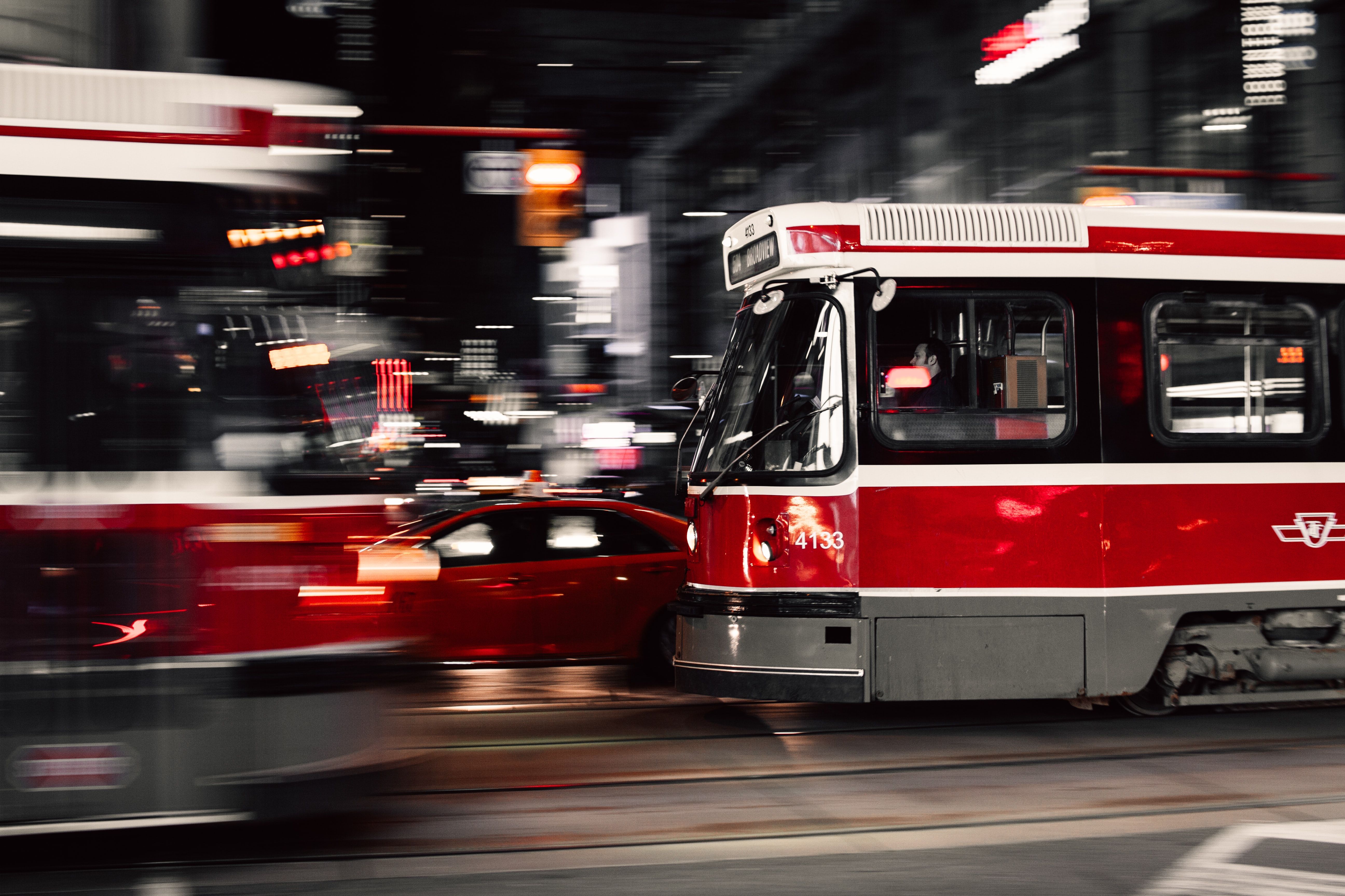 Streetcars speed by on a fash road downtown