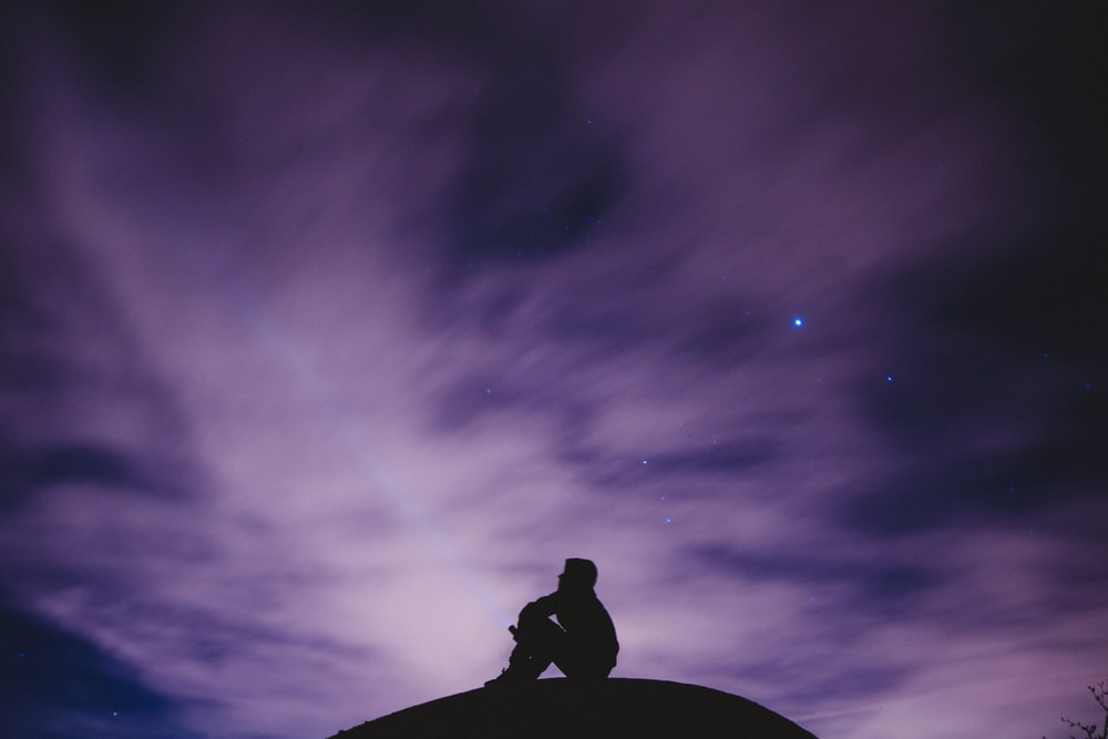 person sitting on black surface looking to sky