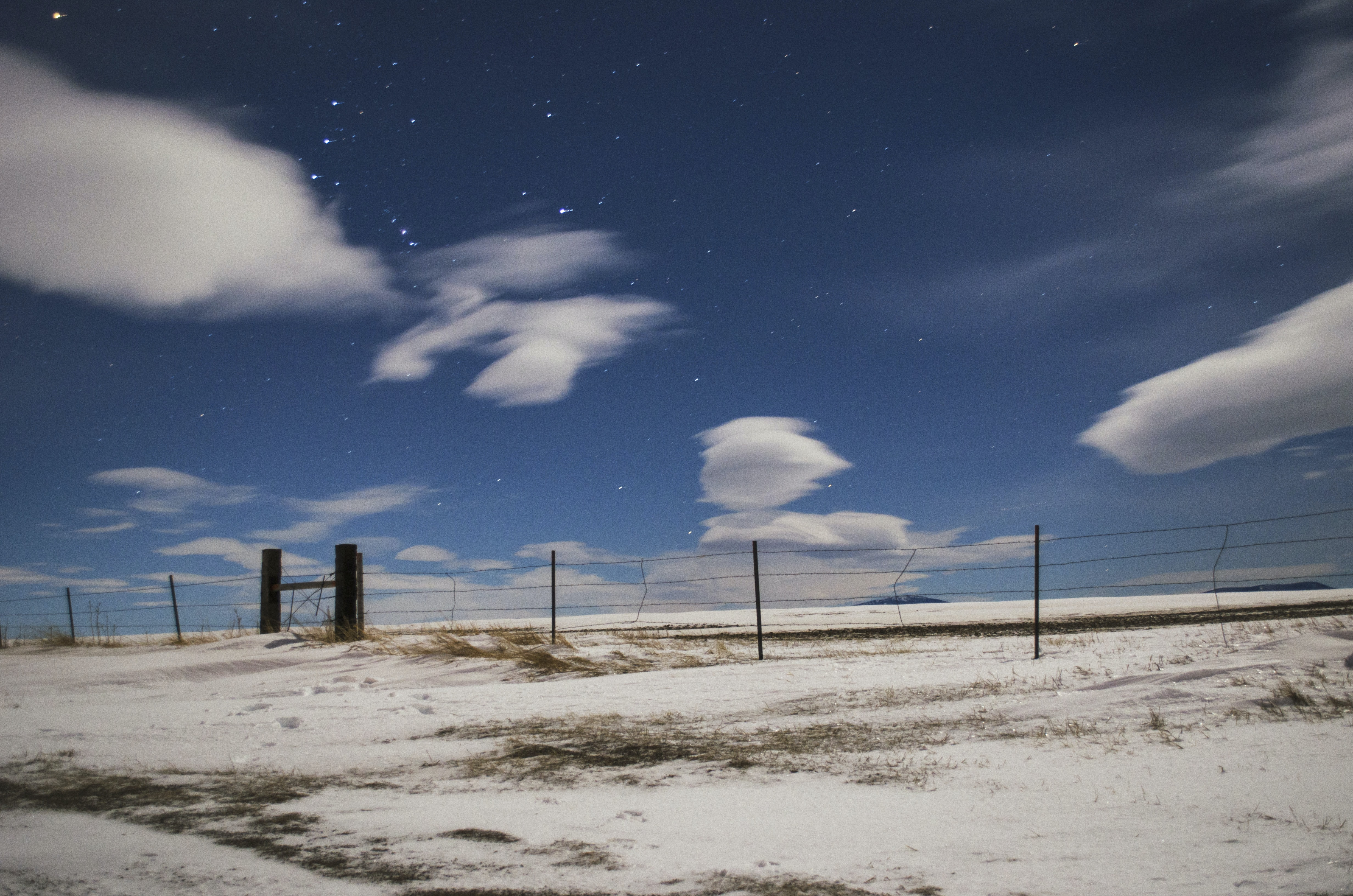 View of the cloudy star speckled sky at a fence near Great Falls