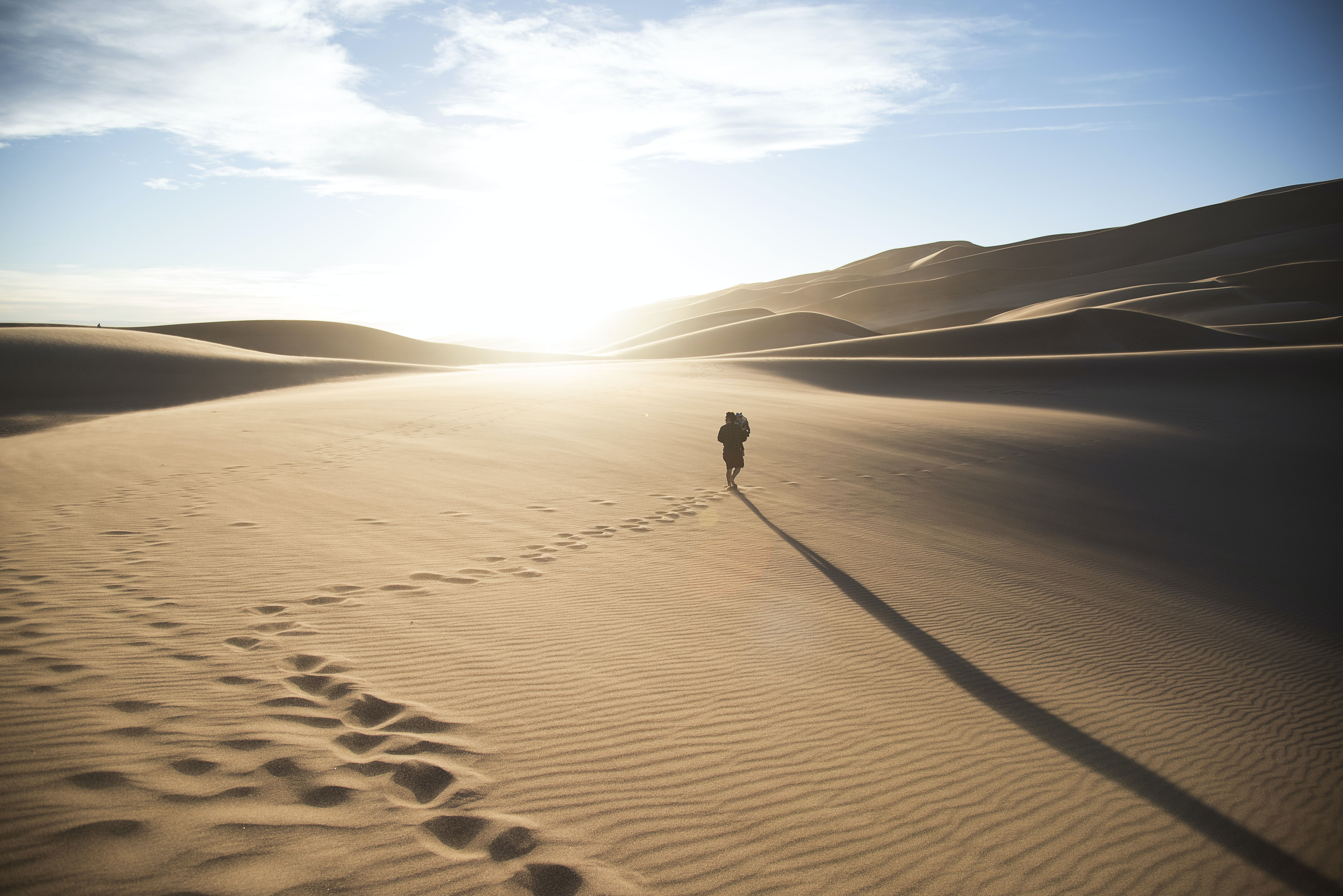 A person walking through the sand, leaving footprints on the dunes at Great Sand Dunes National Park and Preserve