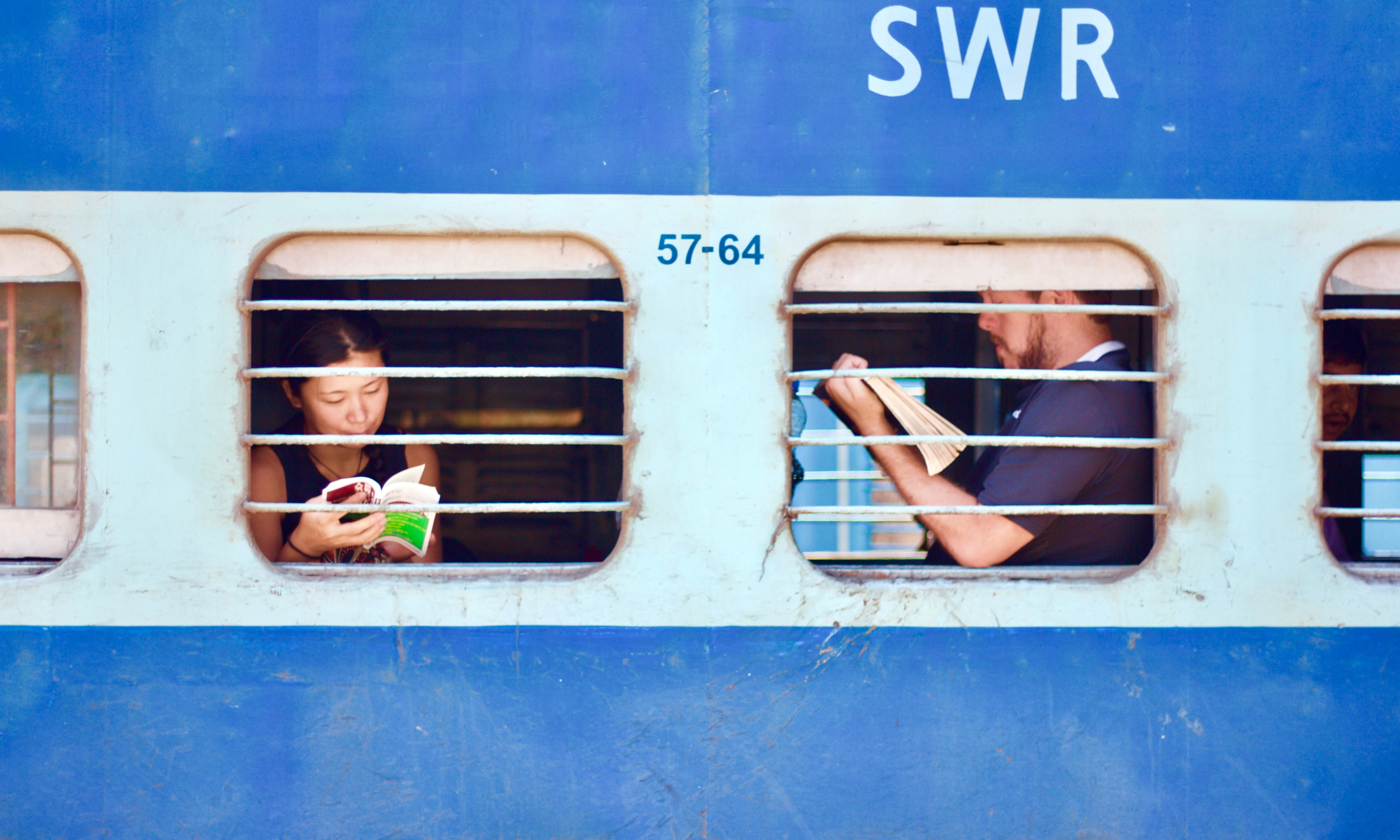 Two people reading books on an old train seen through its windows
