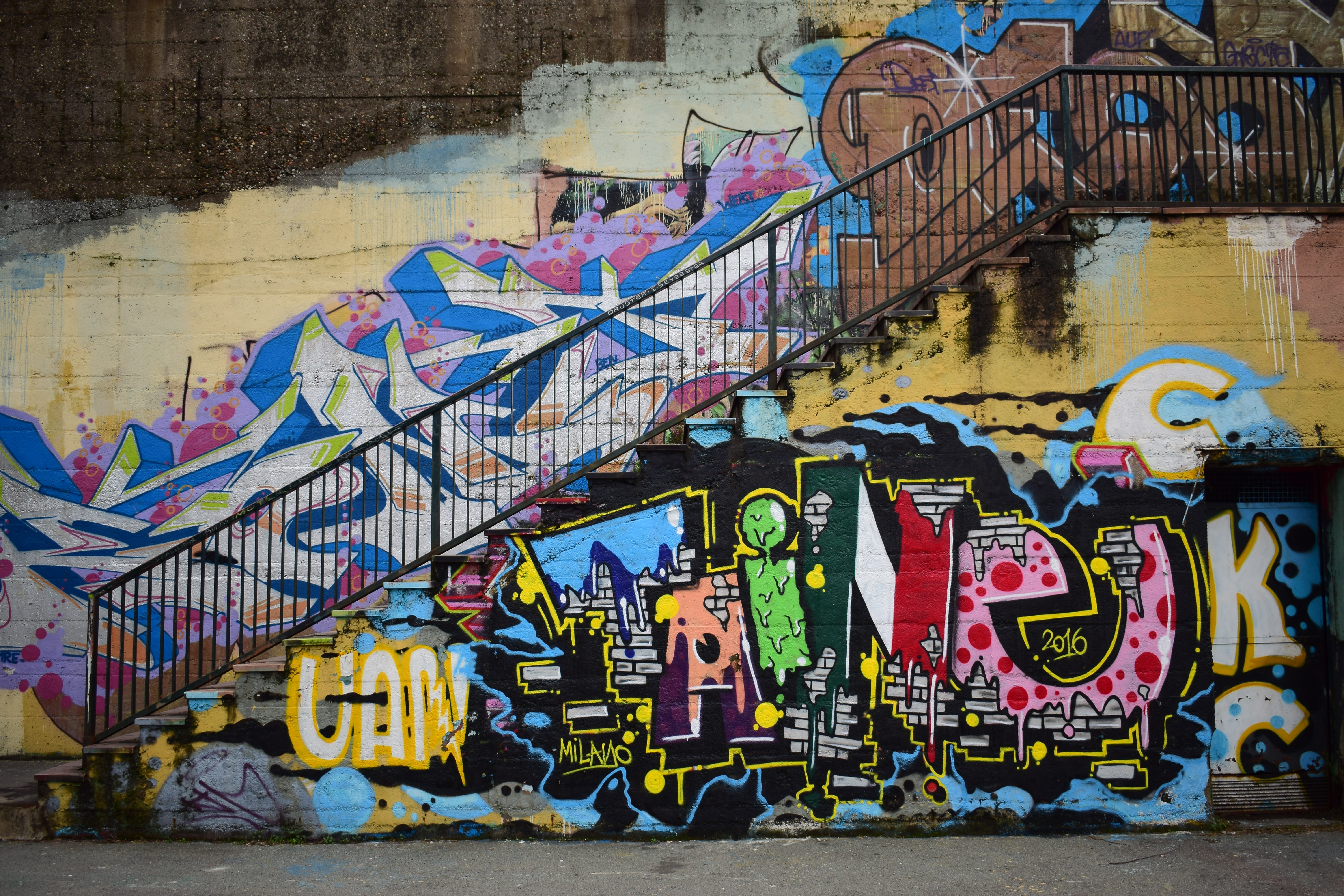 Urban stairs and railing with colorful grunge graffiti covered walls