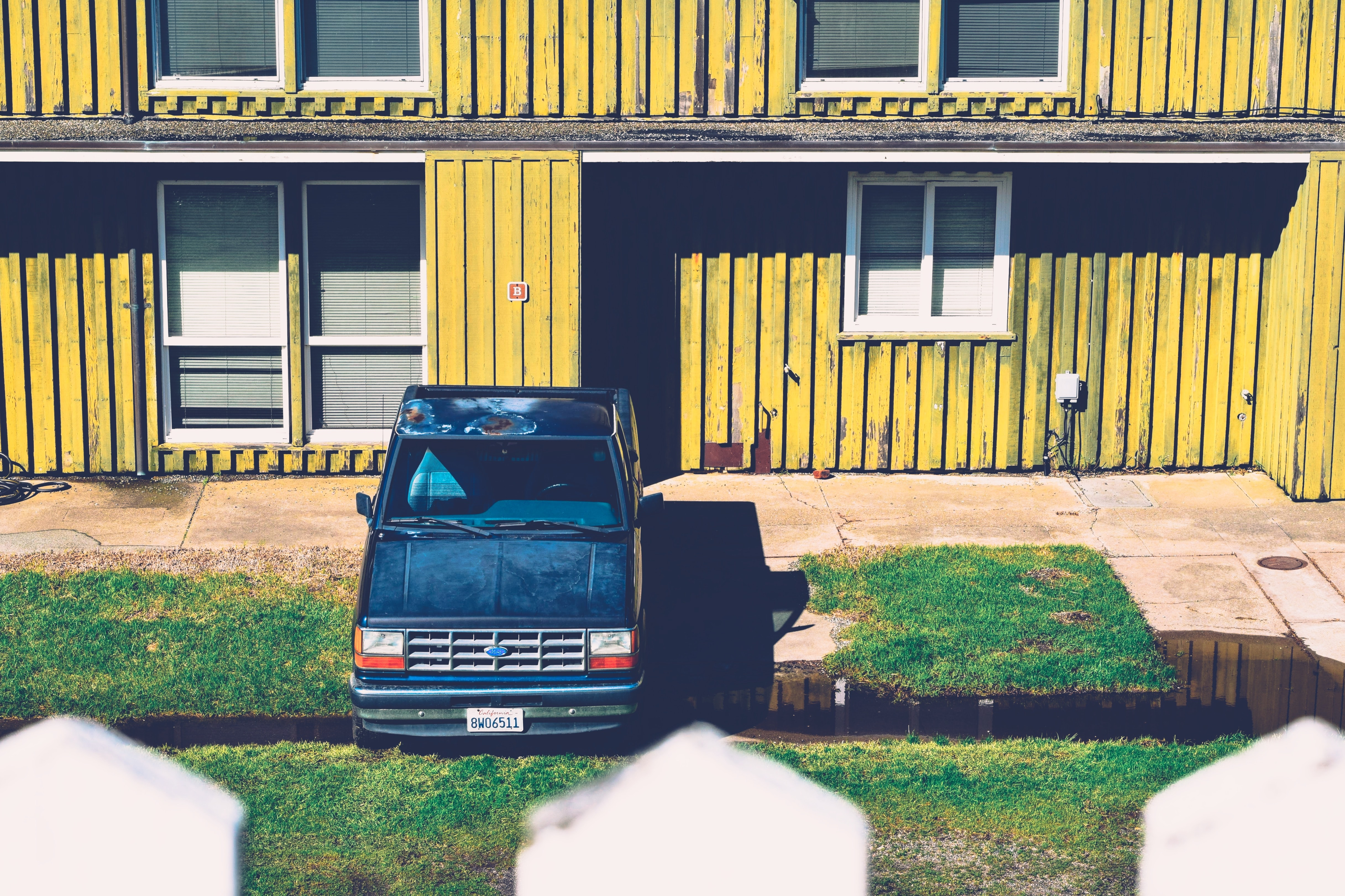 A blue truck with rust casts a shadow on the lawn of a yellow building