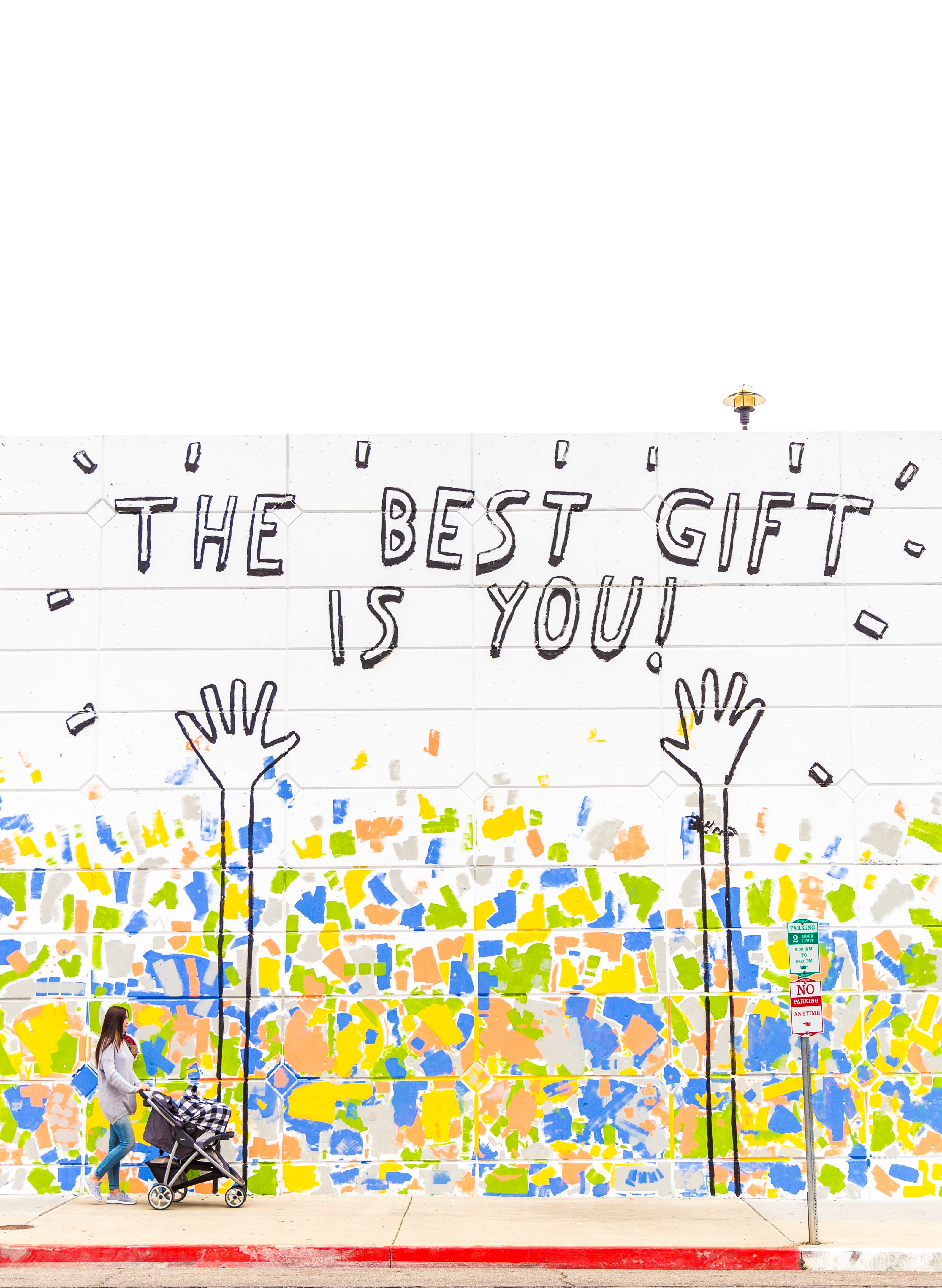 "Woman pushing a stroller passes mural that reads ""The best gift is you"""