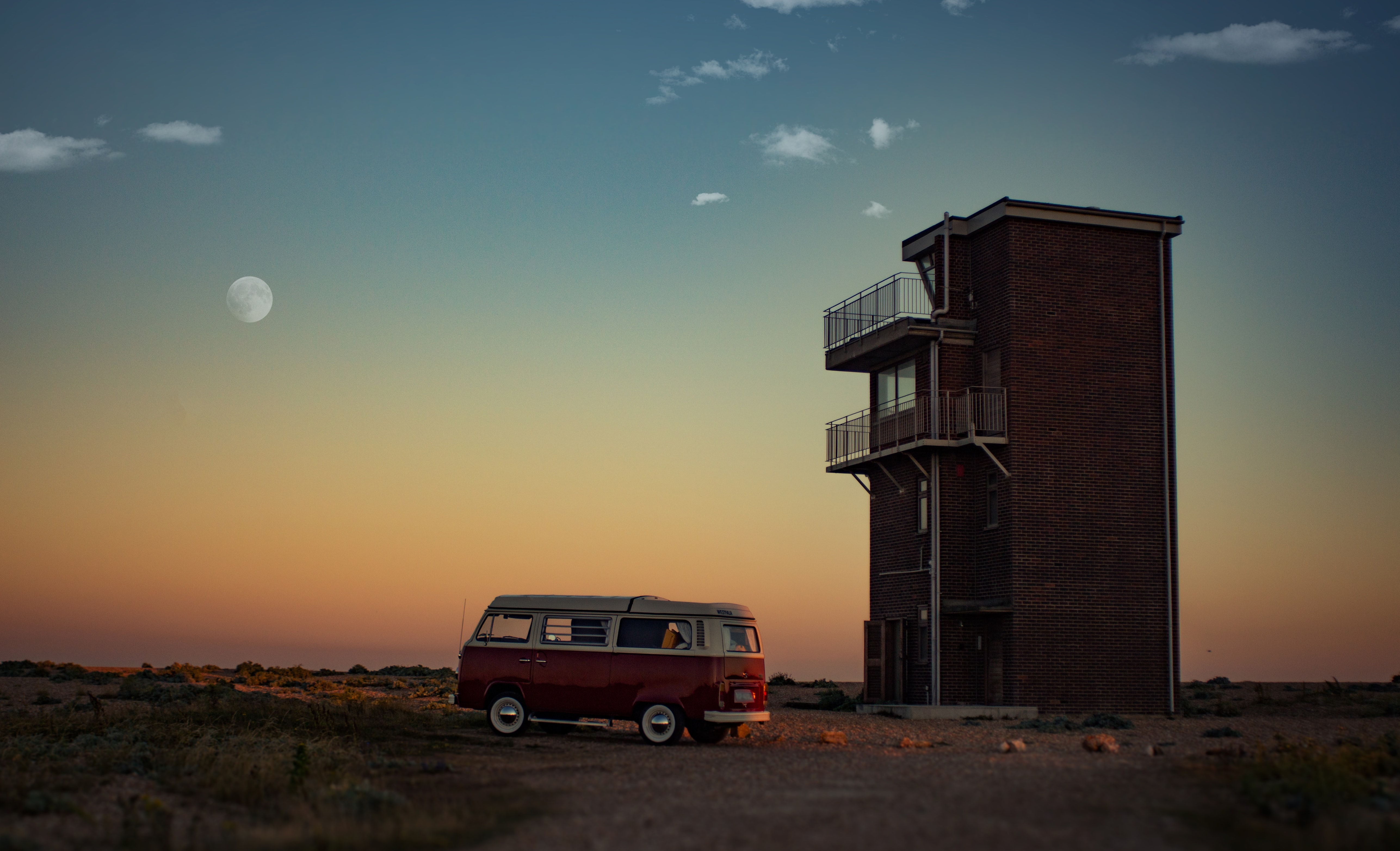 Volkswagen campervan parked next to a standalone building in Dungeness a dawn-or-dusk with a faint moon in the orange-fading-to-blue sky