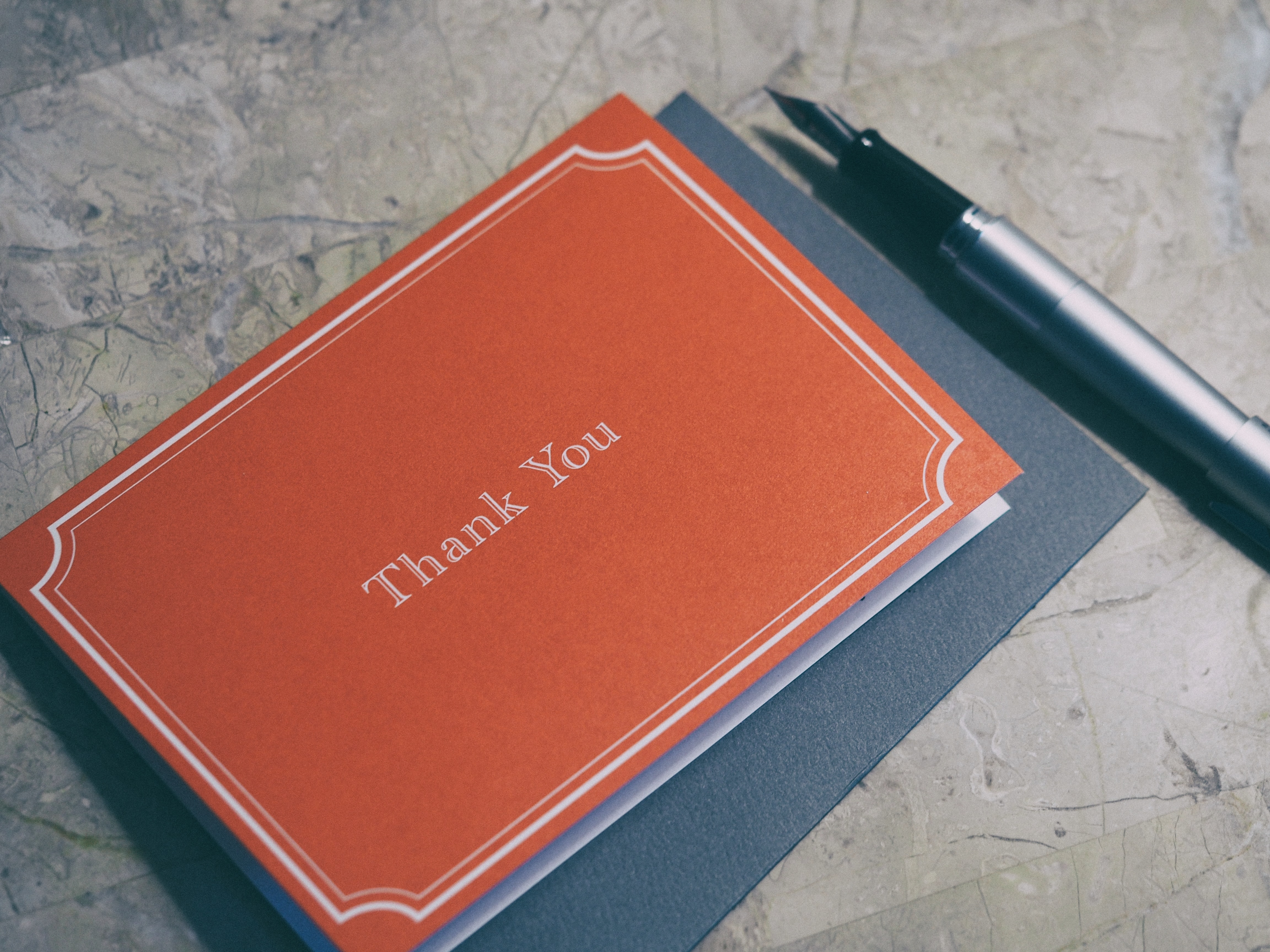 A fountain pen next to a red thank you card