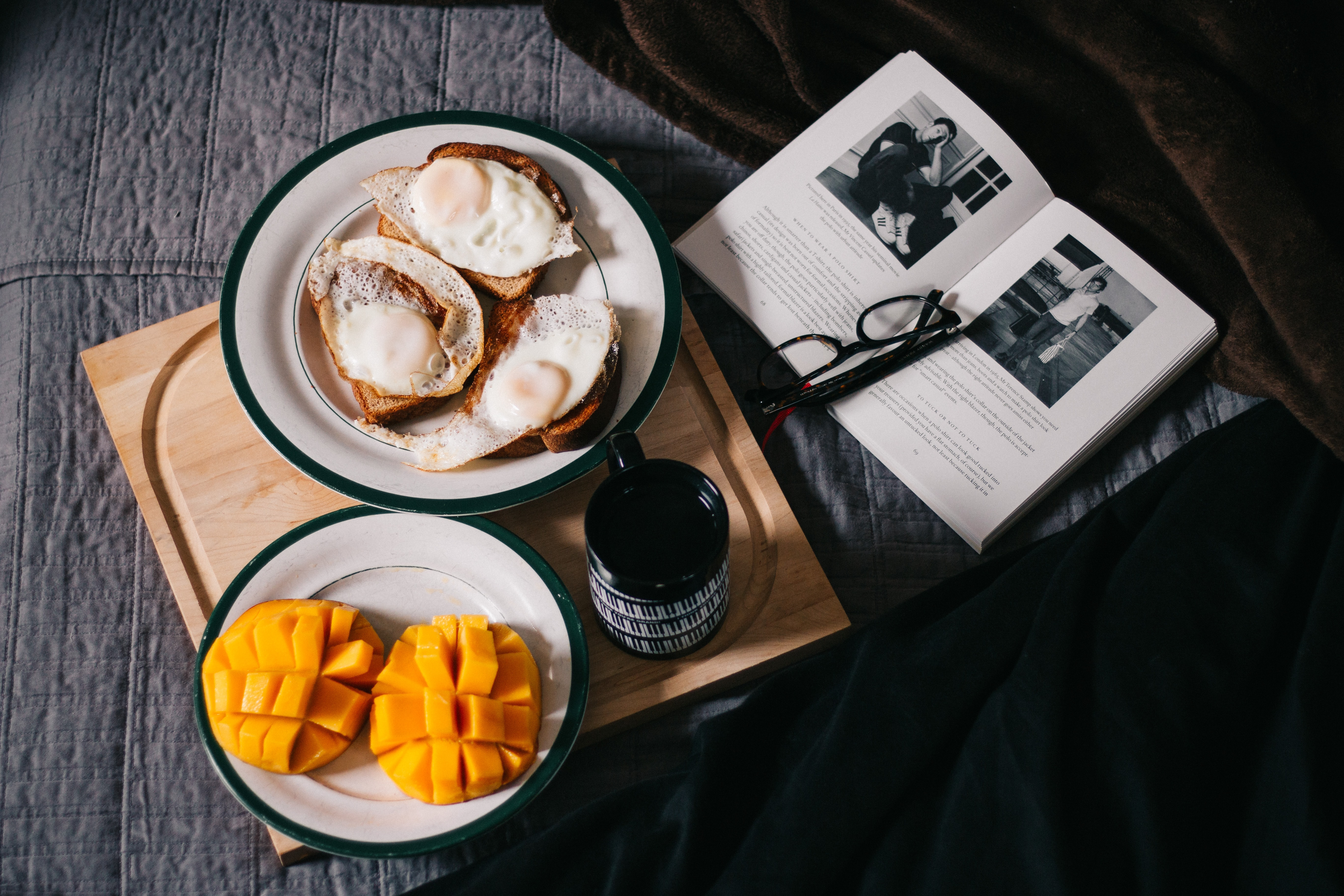 A breakfast spread including mango, fried eggs, and coffee on a wooden serving board next to a book and glasses on a bed