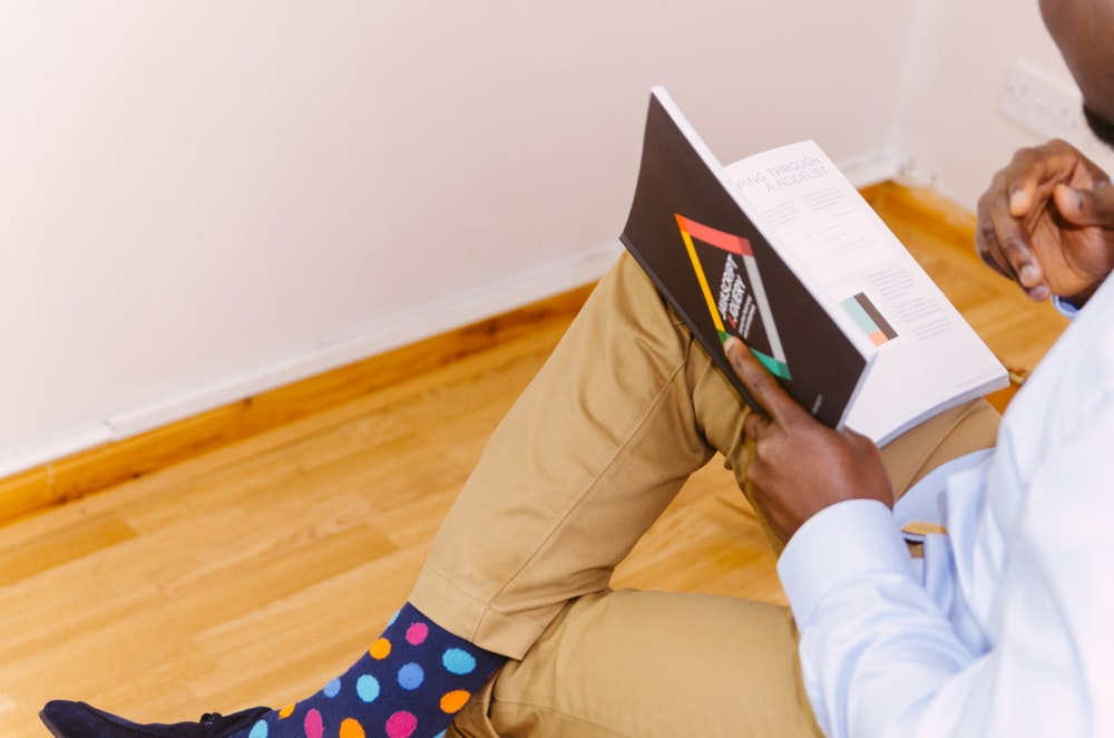 person sitting while reading book