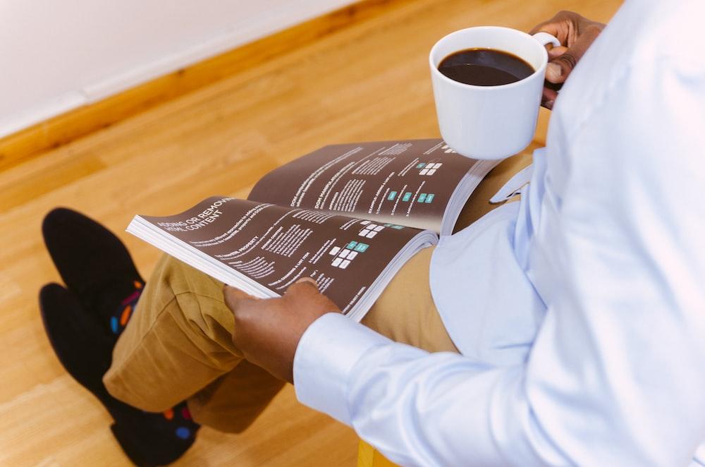 man holding coffee mug and reading magazine