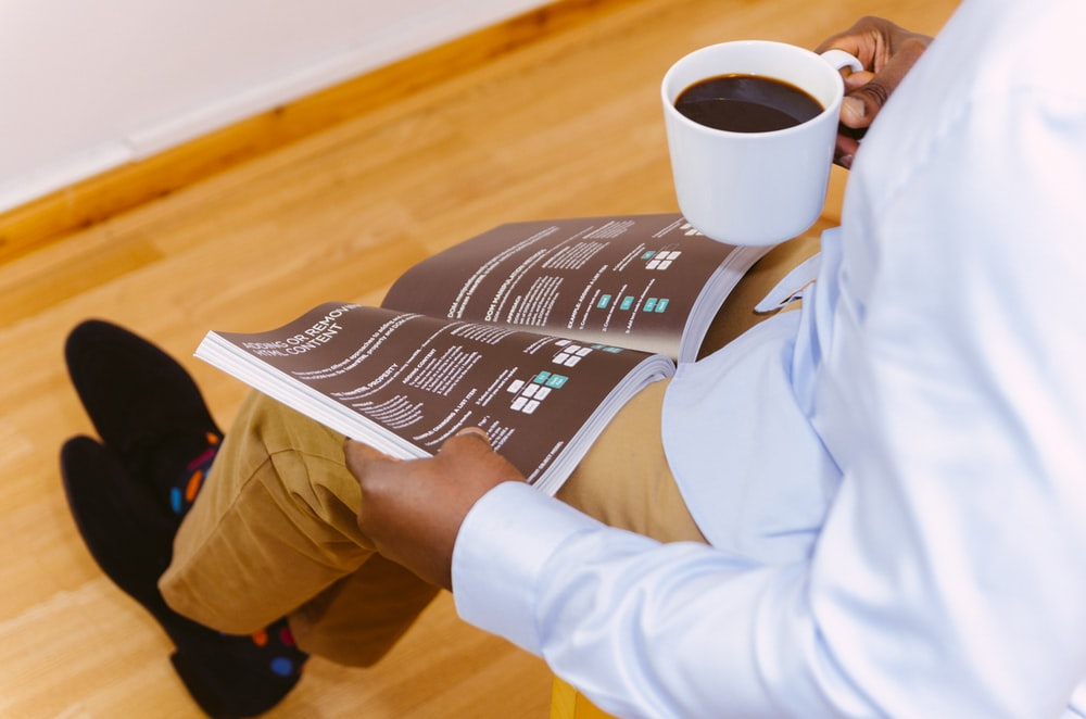 man holding coffee mug and reading magazine