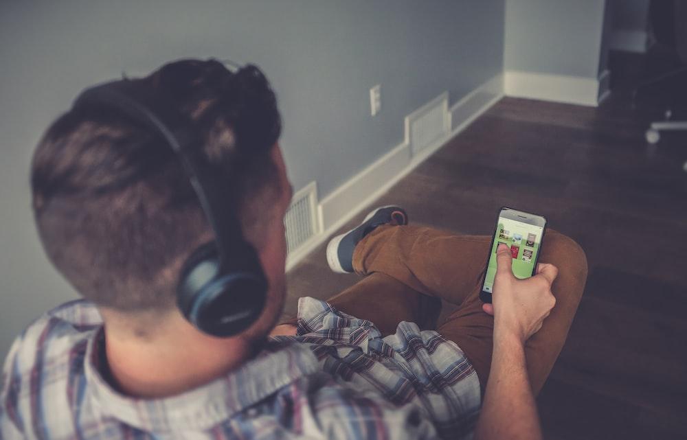 man using smartphone while using headphones