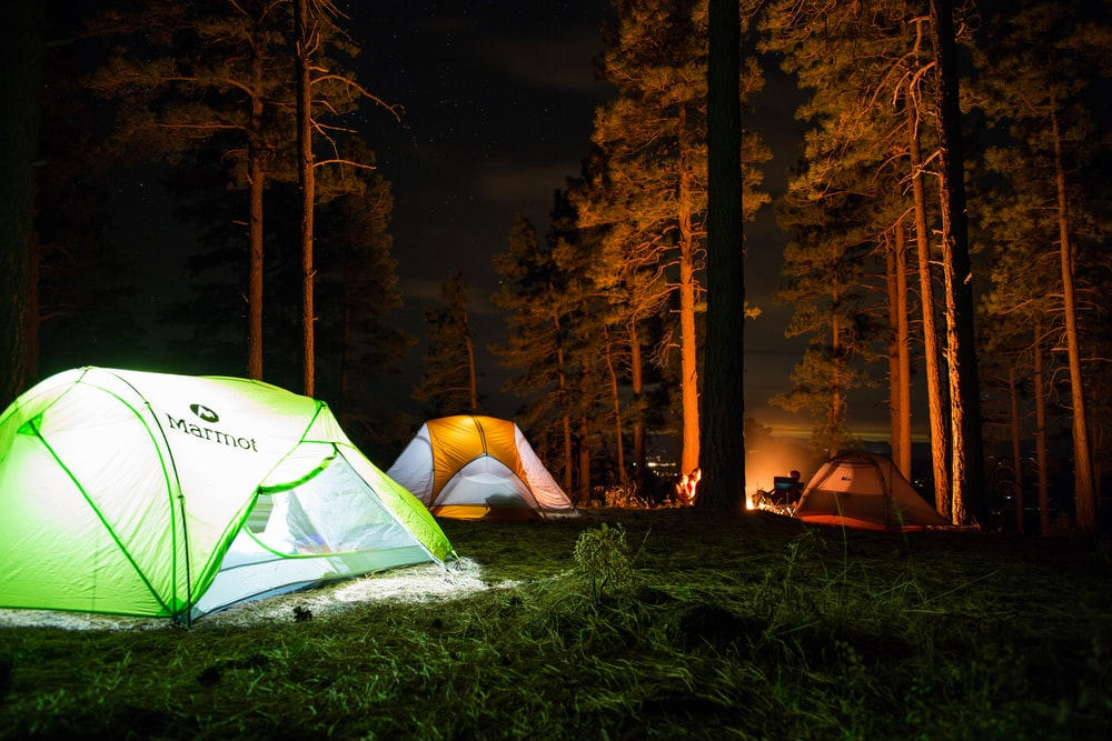 three dome tents with lights on forest beside campfire