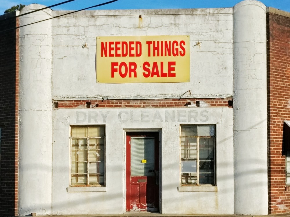 needed things for sale poster posted on white concrete establishment