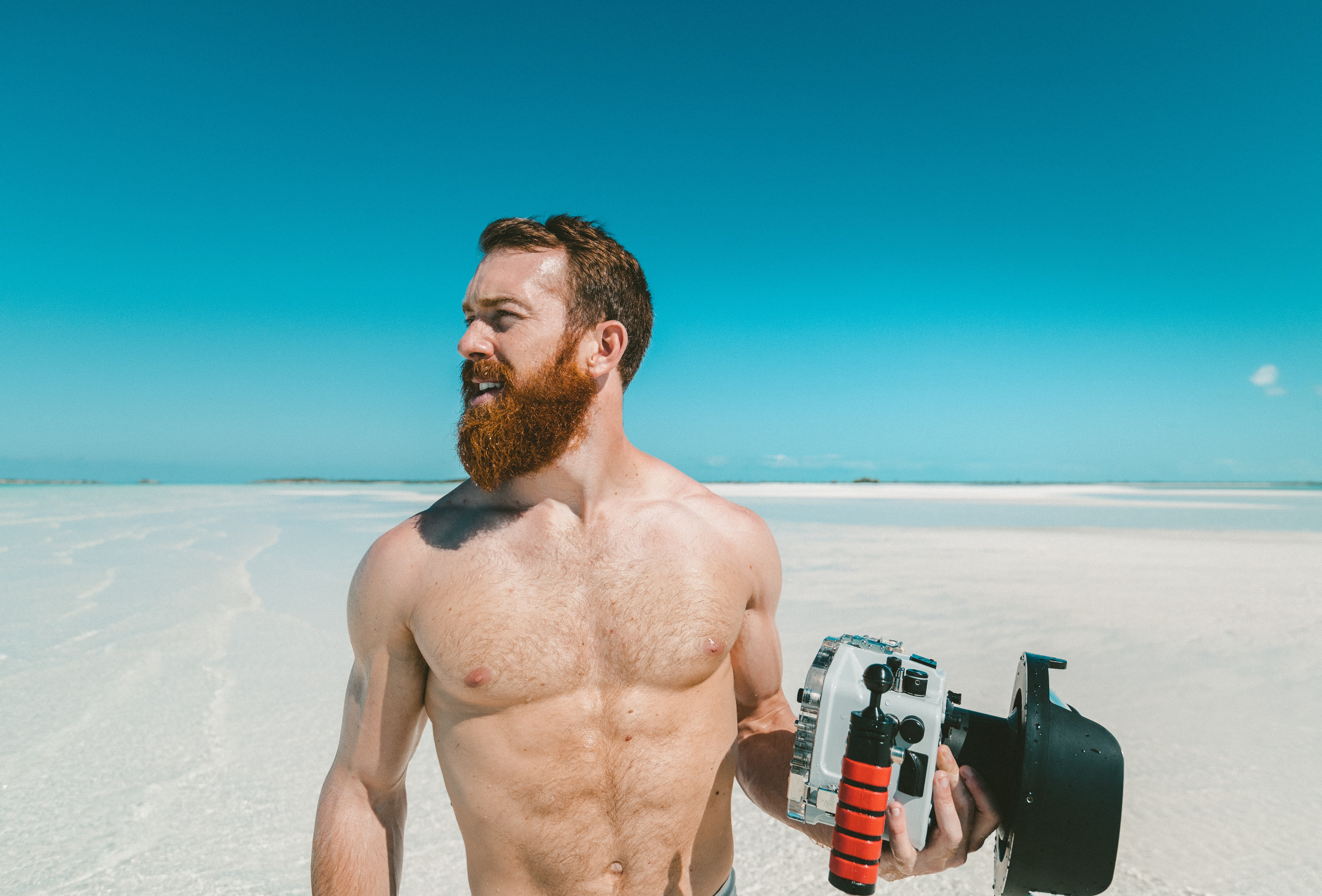 Man with a beard holding an underwater camera at the sand beach