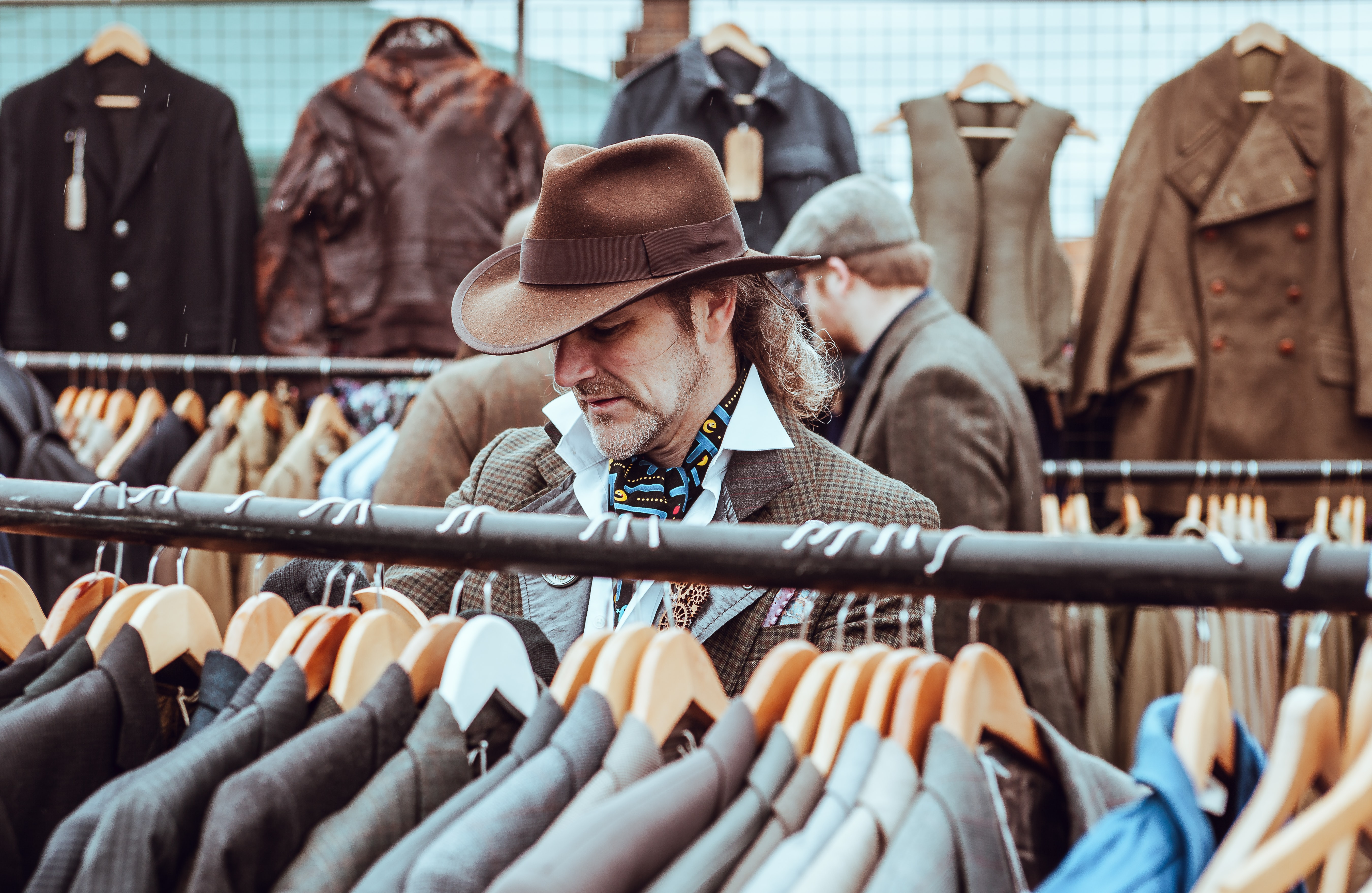 A man in a hat browsing suit jackets in a store