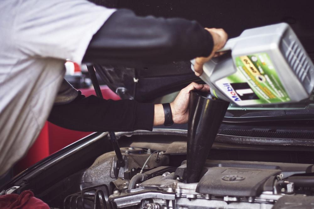 man refilling motor oil on car engine bay