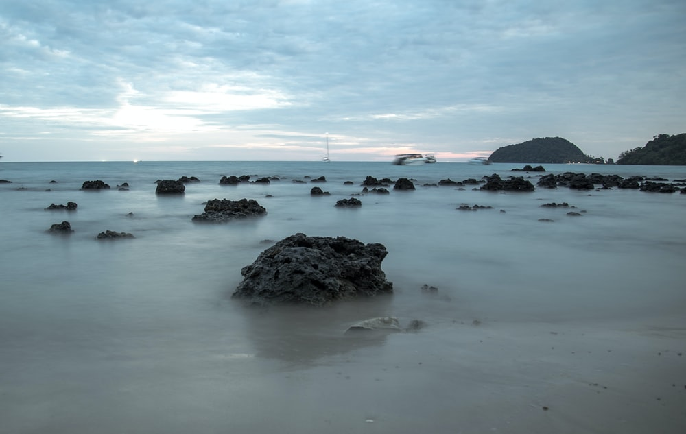 black rock formation on sea shore during daytime